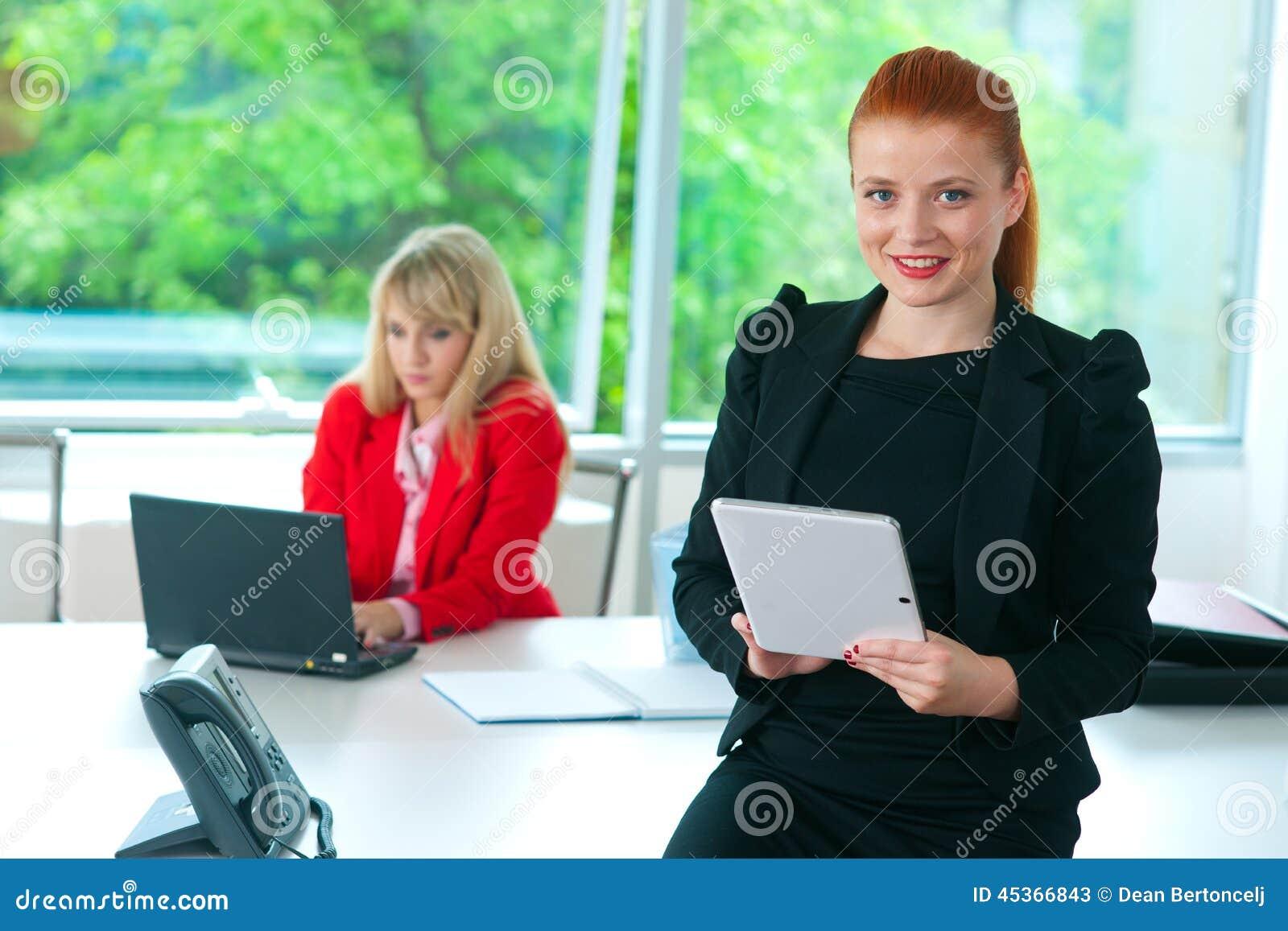 Femme attirante d affaires dans le bureau avec le comprimé