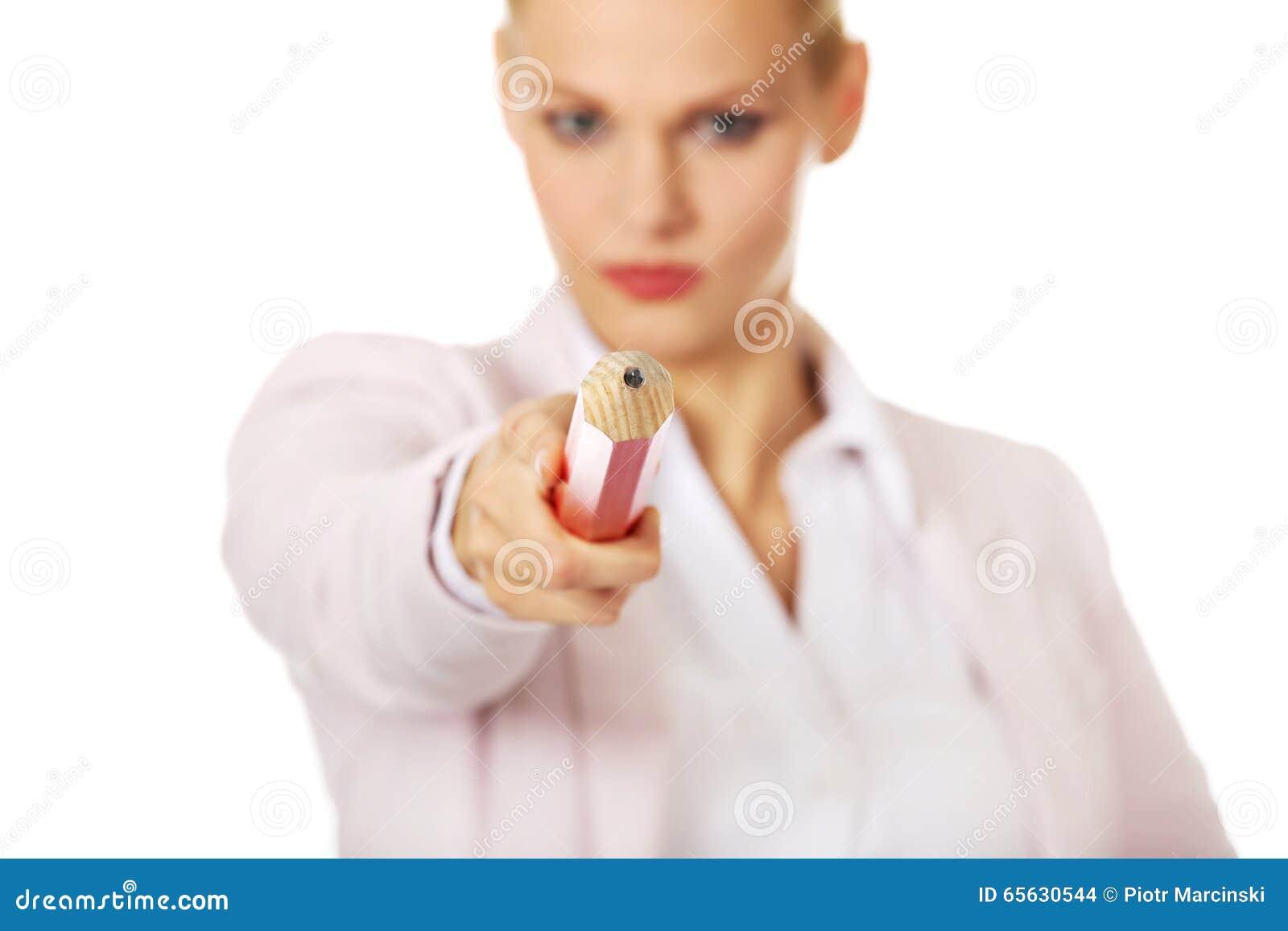 Femme attirante d affaires se dirigeant sur l appareil-photo avec le stylo surdimensionné