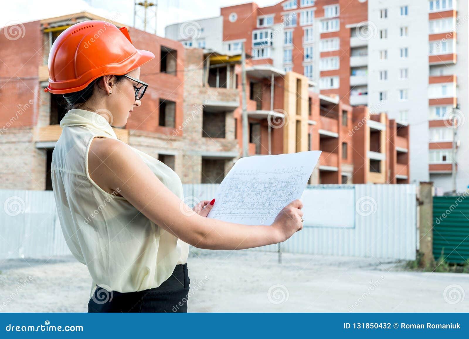 Femme attirante dans le casque de constructeur regardant le modèle