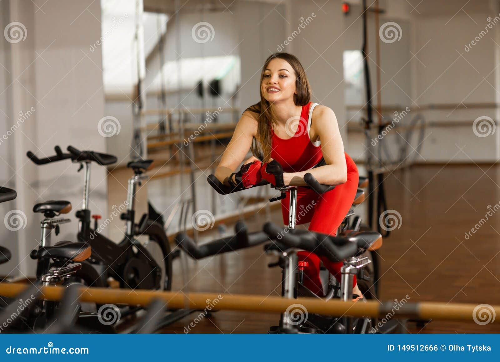 Femme attirante dans un costume rouge de sports dans le gymnase, montant sur le vélo stationnaire de vitesse R?flexion dans le mi