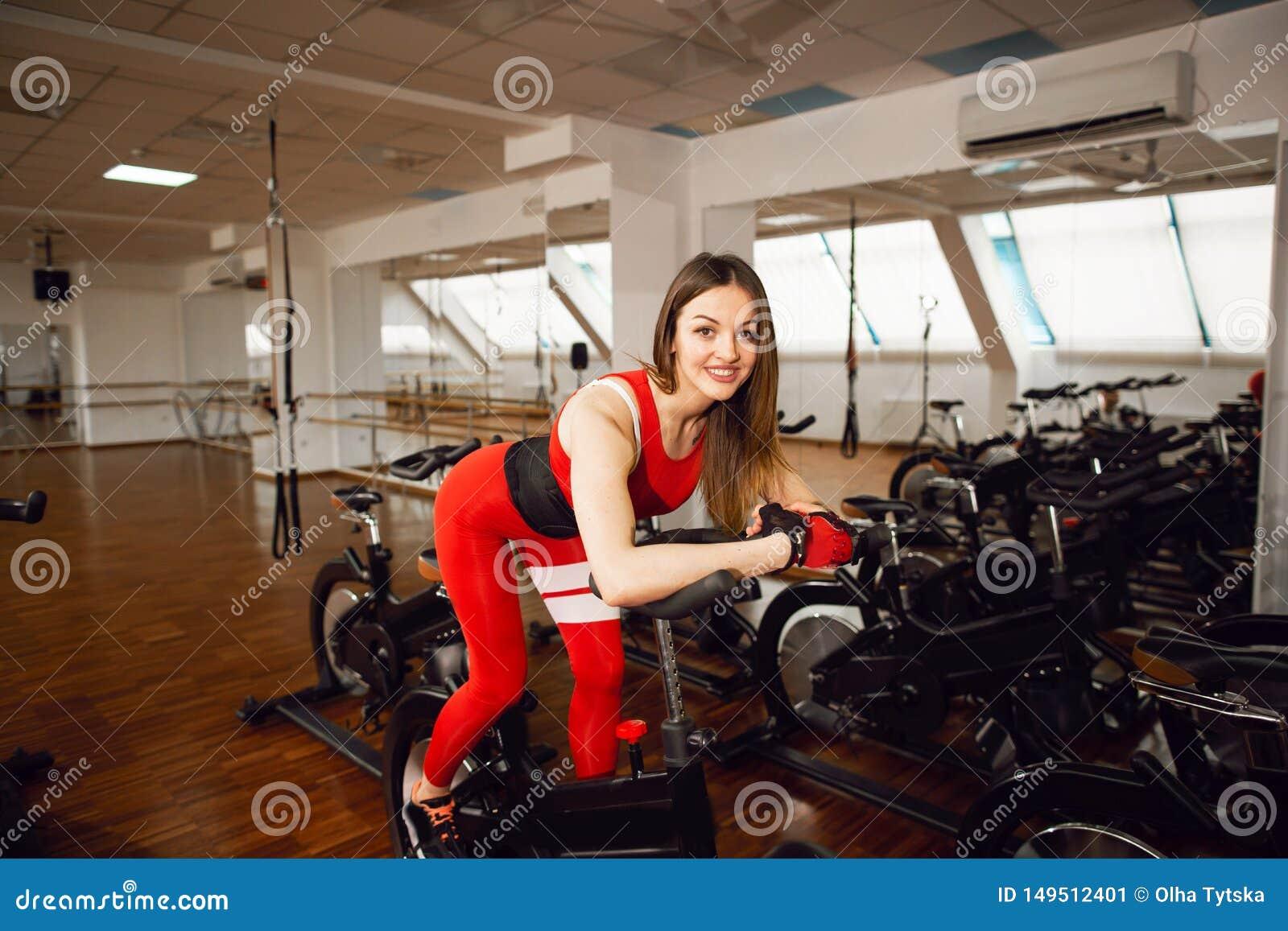 Femme attirante dans un costume rouge de sports dans le gymnase, montant sur le vélo stationnaire de vitesse Style de vie sain
