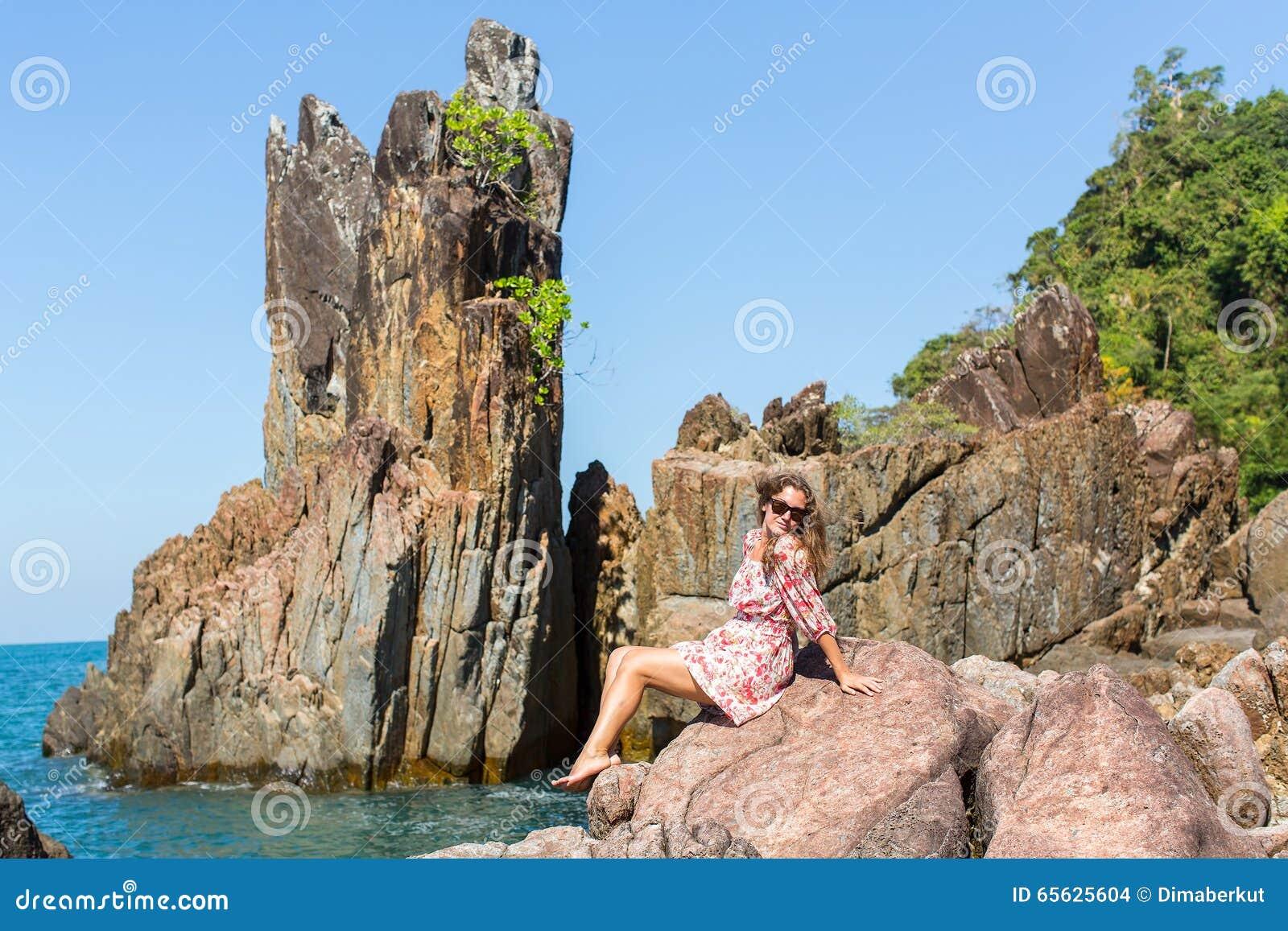 Femme attirante s asseyant aux roches près de la mer