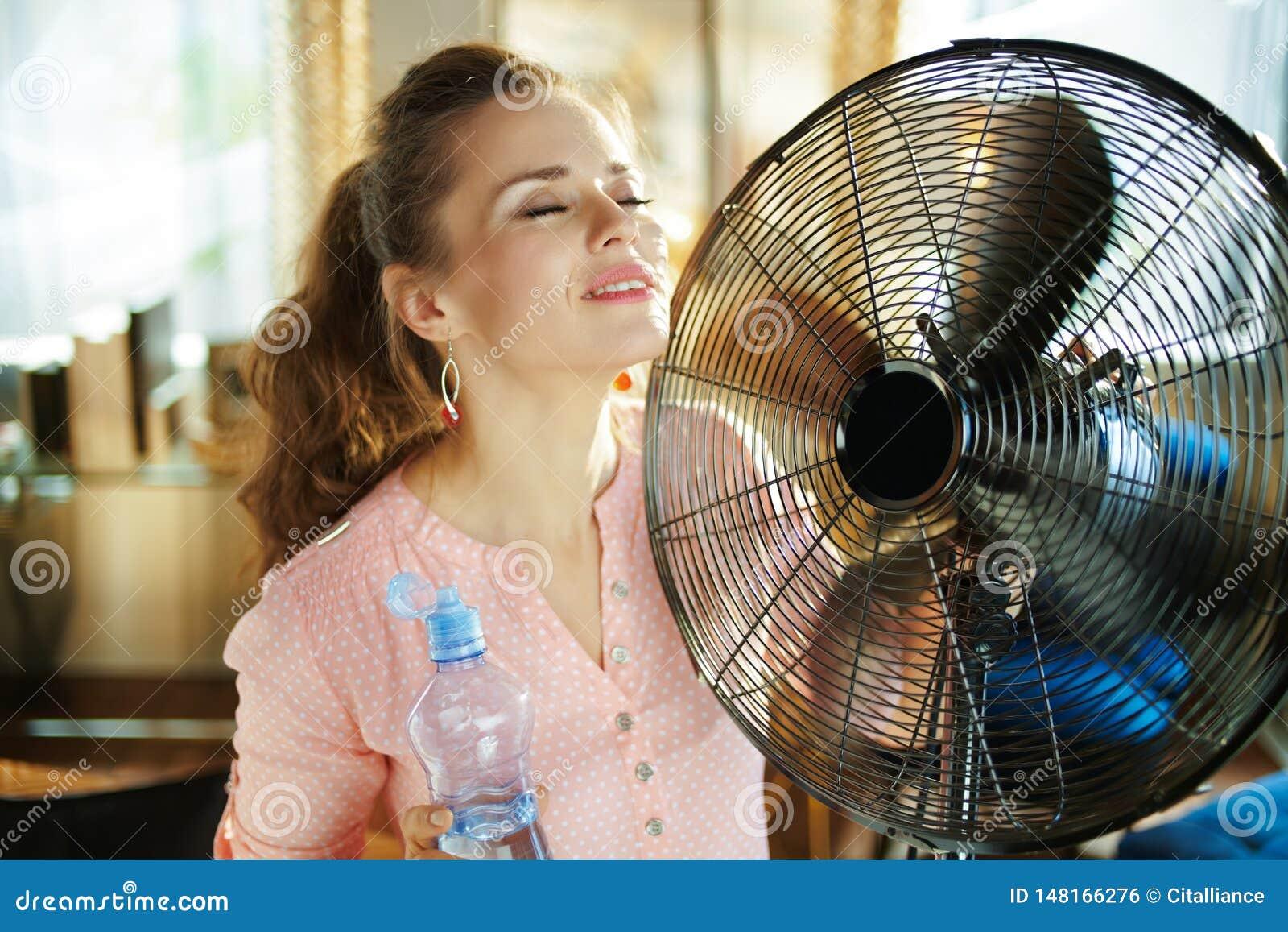 Femme au foyer avec la bouteille froide de l eau utilisant la fan
