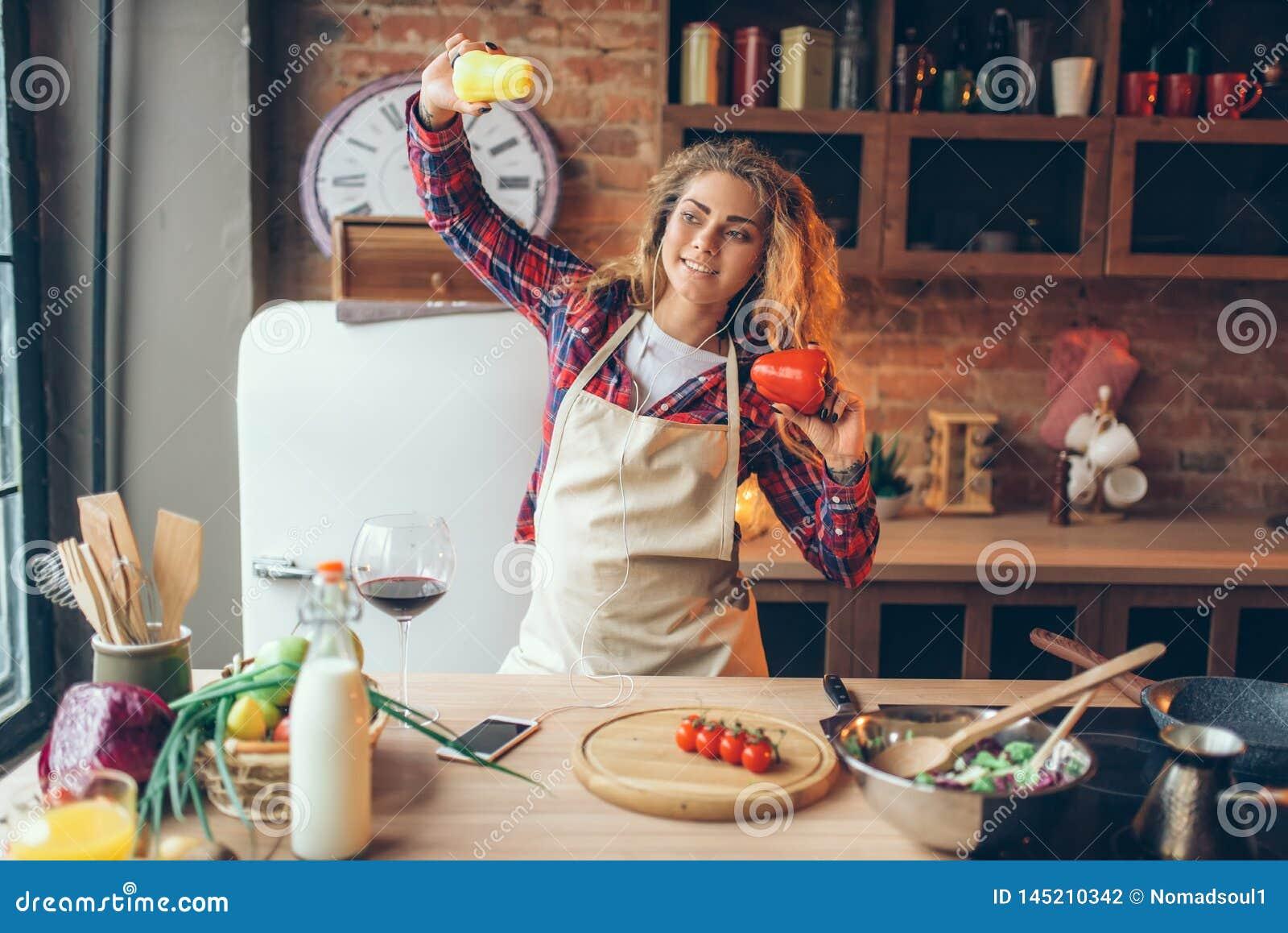 Femme au foyer dans les écouteurs et la danse de tablier sur la cuisine