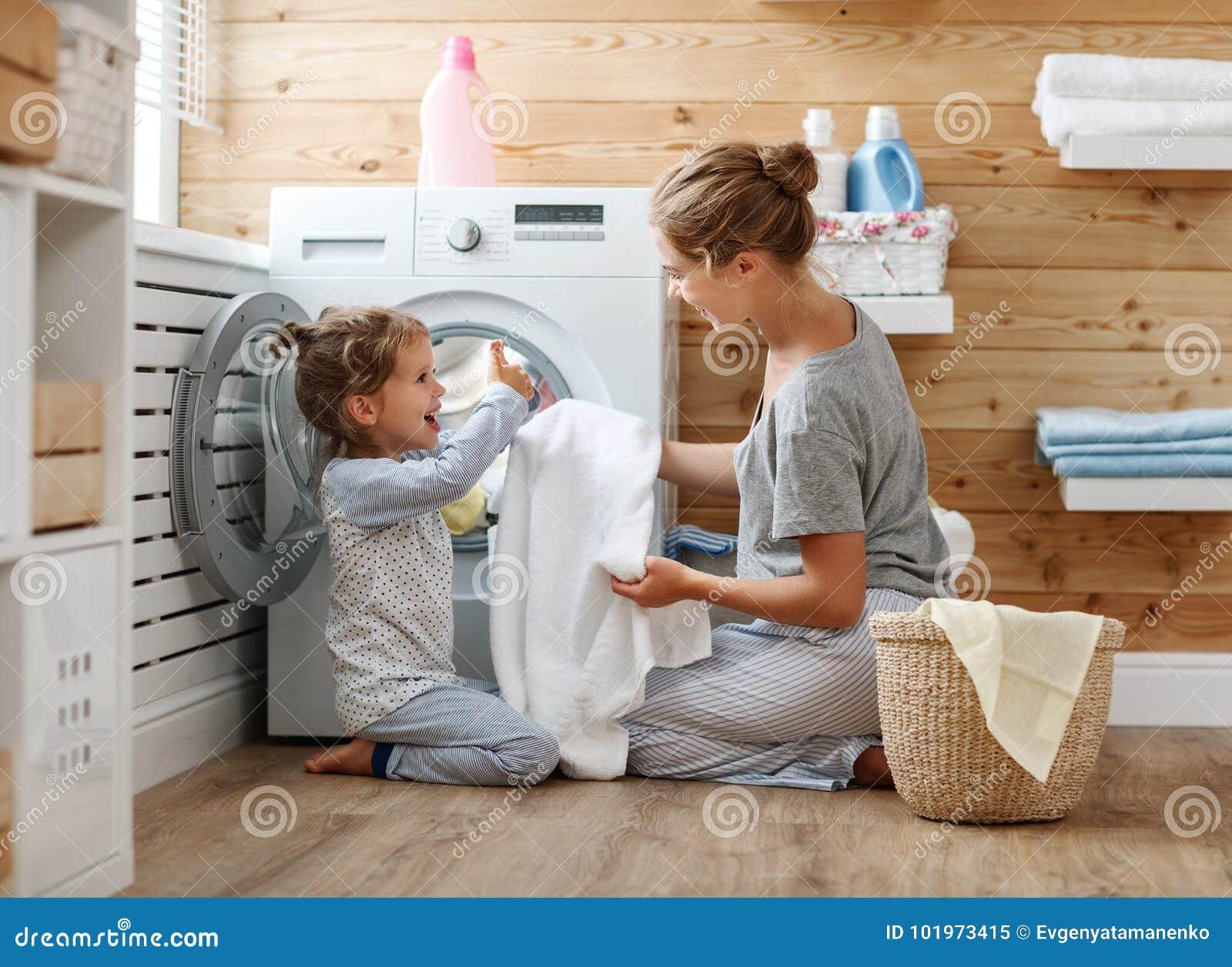 Femme au foyer et enfant heureux de mère de famille dans la blanchisserie avec le washin
