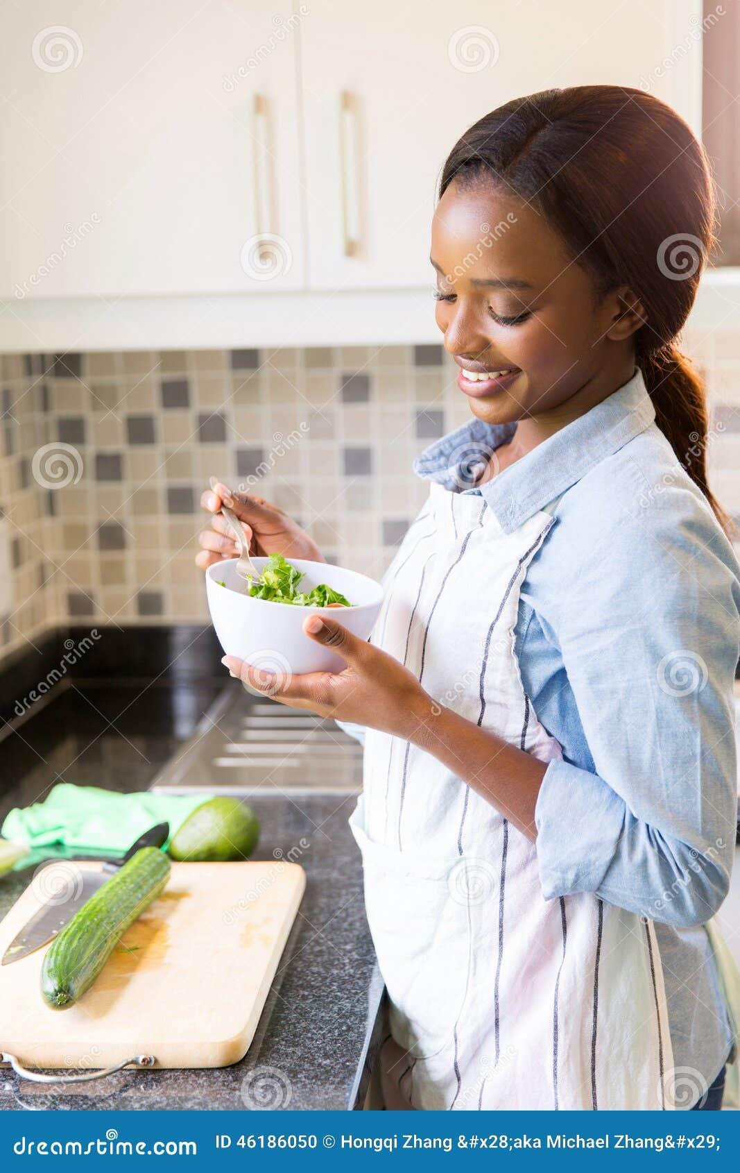 Femme au foyer mangeant de la salade