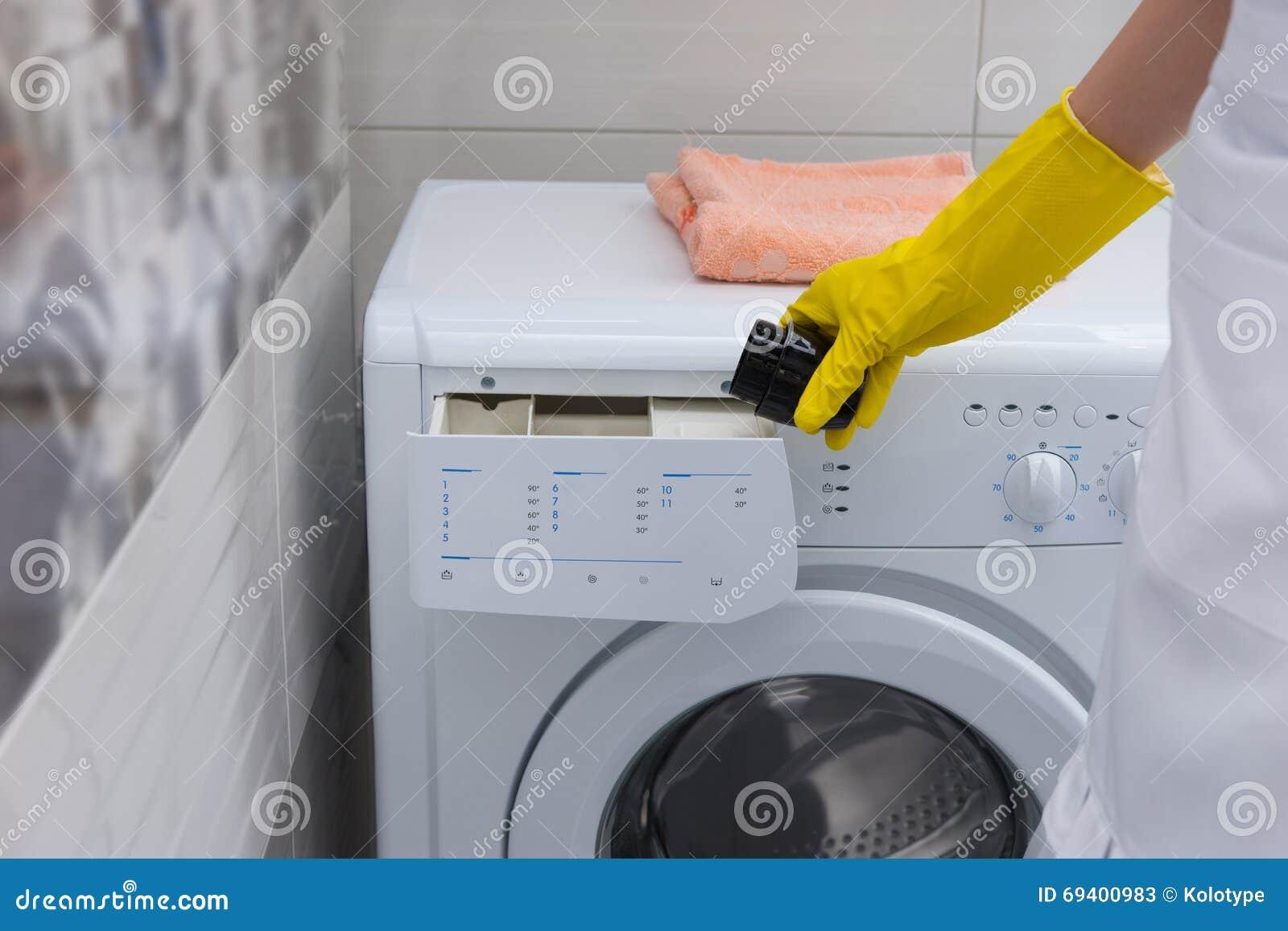 femme au foyer mettant l 39 adoucissant dans une machine laver photo stock image 69400983. Black Bedroom Furniture Sets. Home Design Ideas