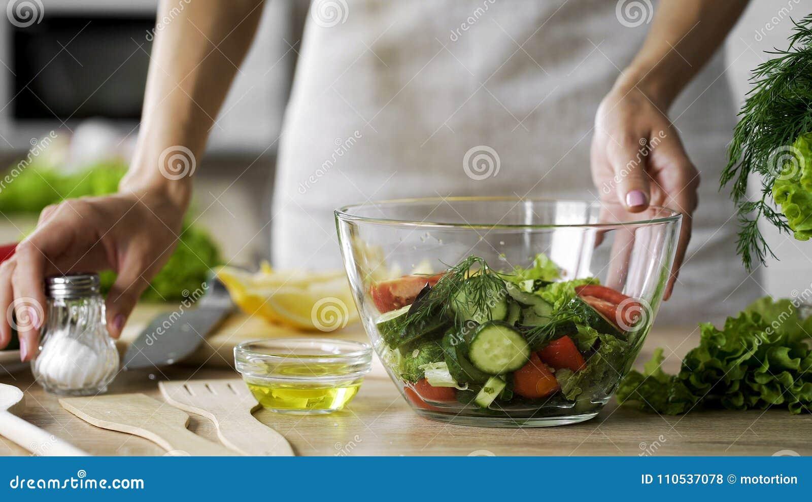 Femme au foyer prenant la salière sur la table pour la salade de assaisonnement de déjeuner, apéritif savoureux