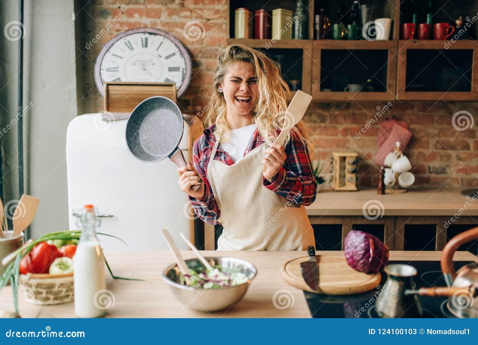 Femme au foyer tenant la poêle et la spatule en bois