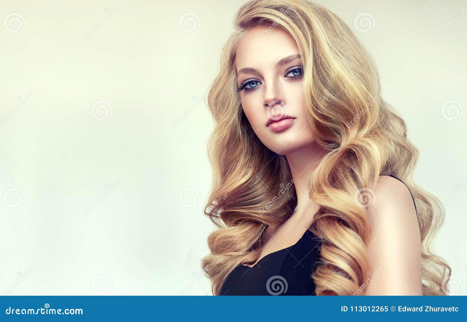 Femme aux cheveux d or avec la coiffure volumineuse, brillante et bouclée Cheveux crépus