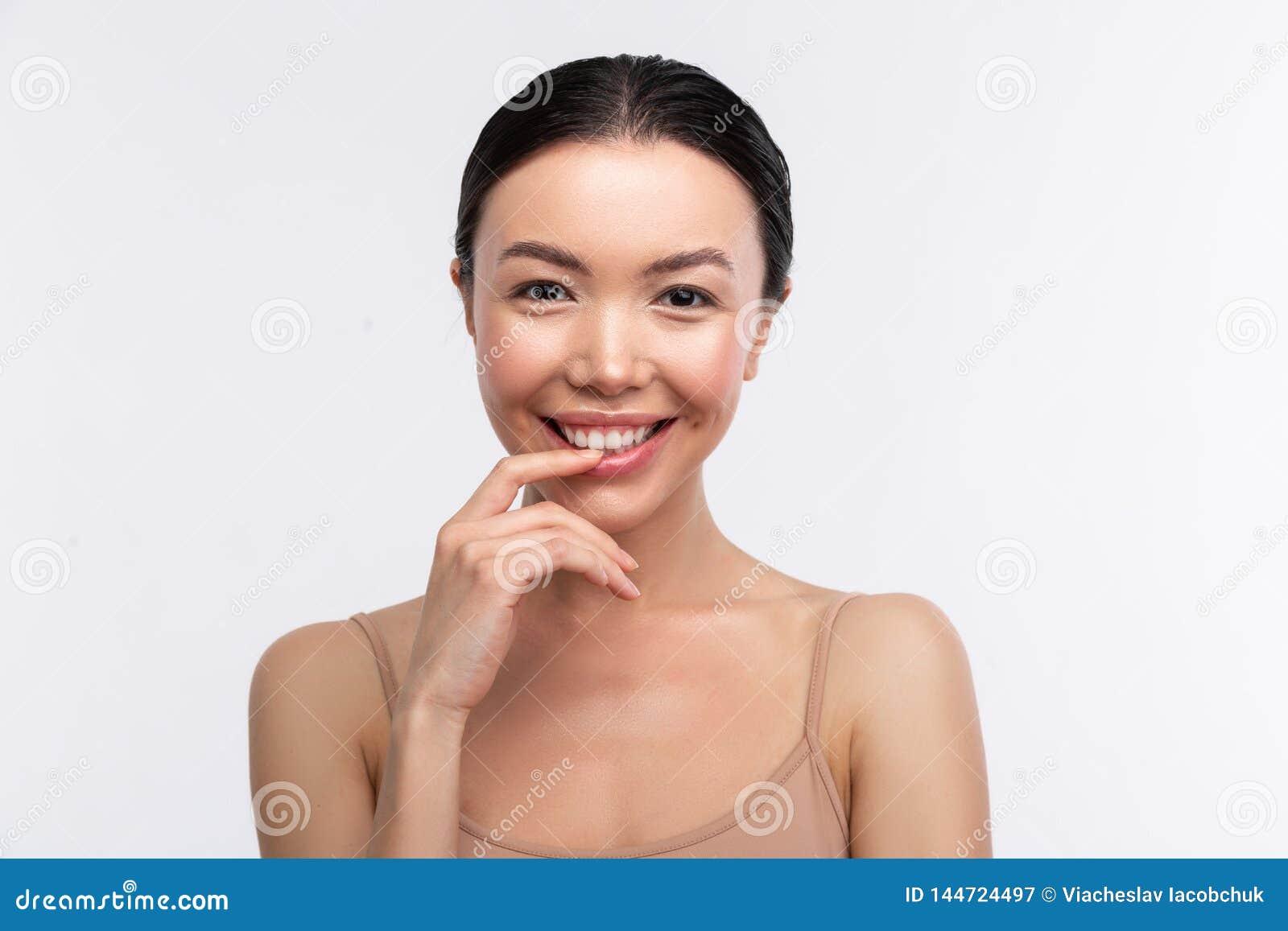 Femme aux yeux noirs utilisant la camisole beige souriant largement