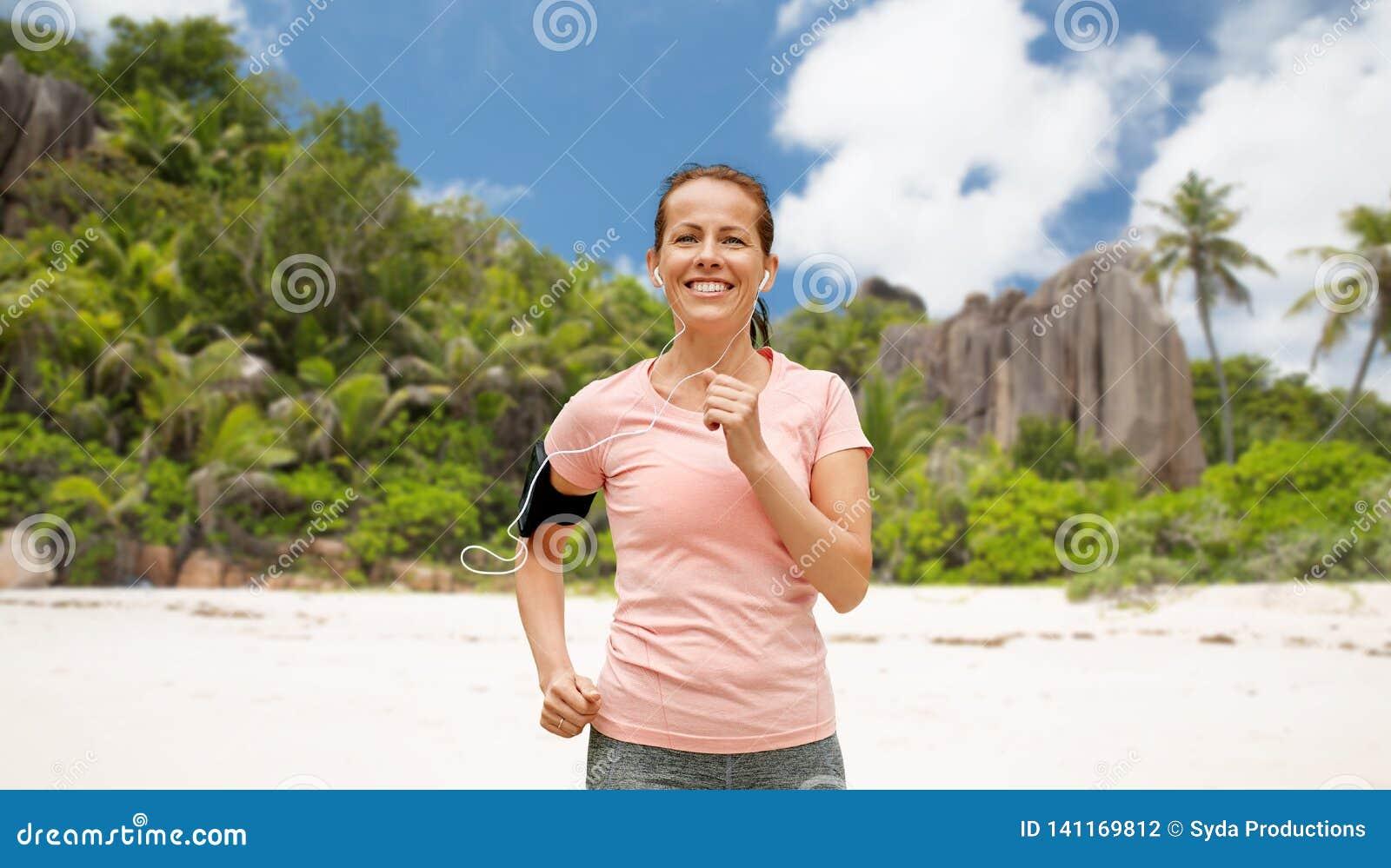 Femme avec des écouteurs et fonctionnement de brassard sur la plage