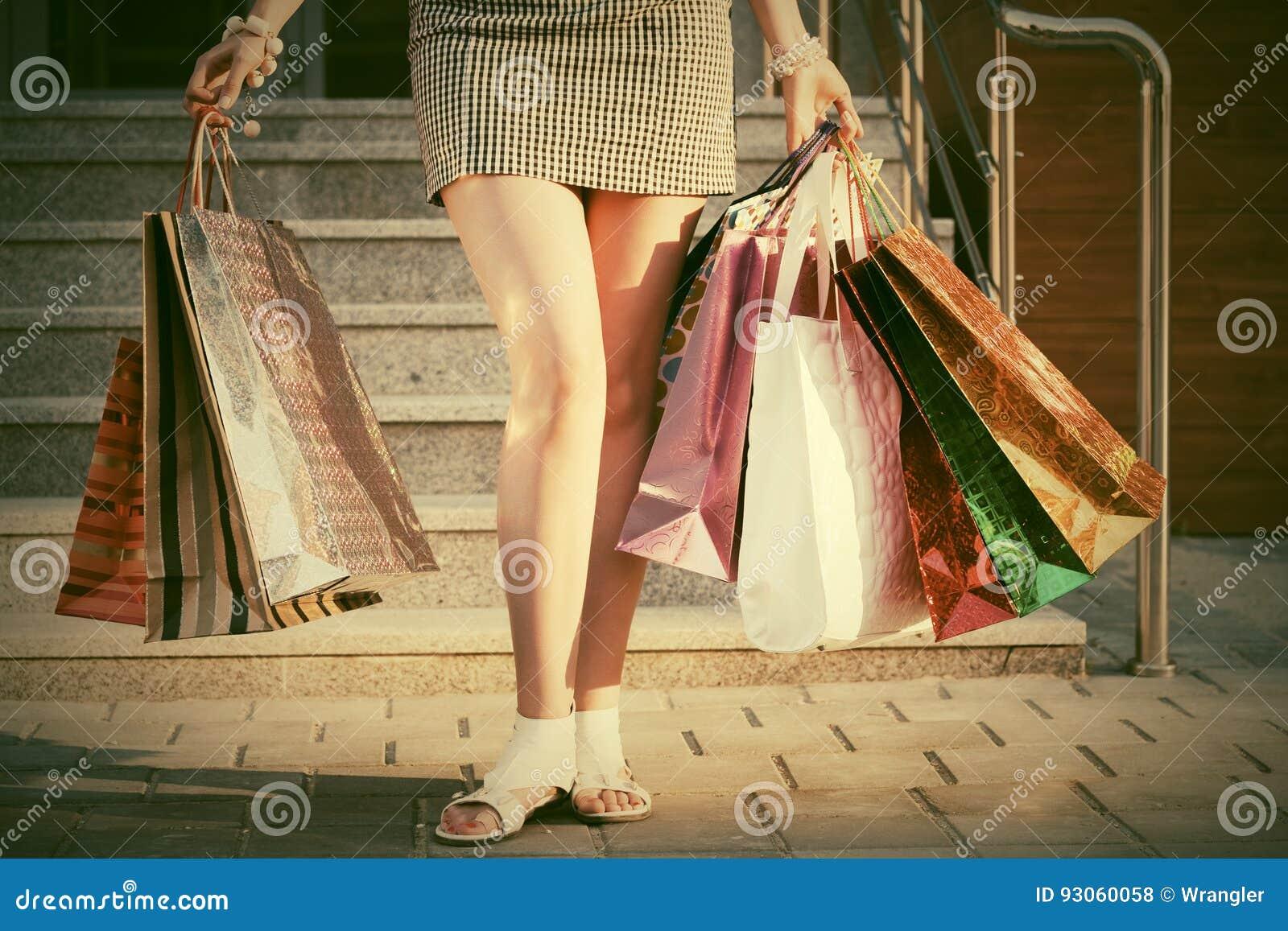 Femme avec des paniers contre un mail