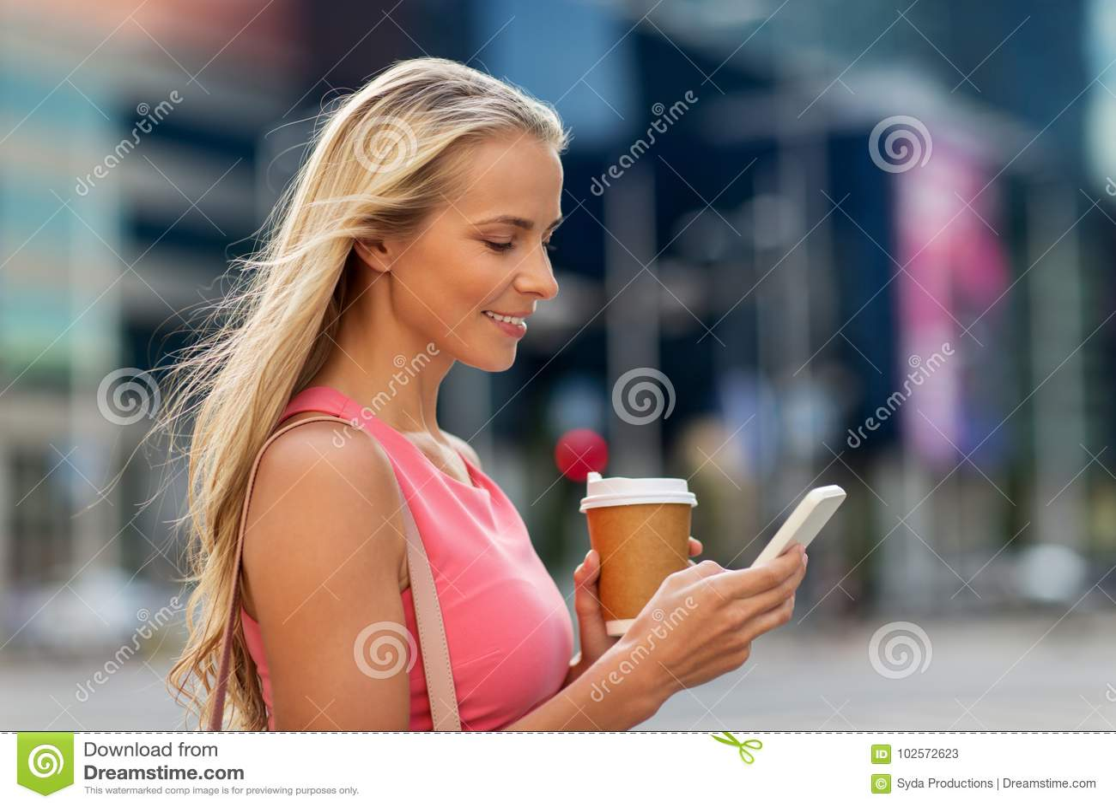 Femme avec du café et le smartphone dans la ville