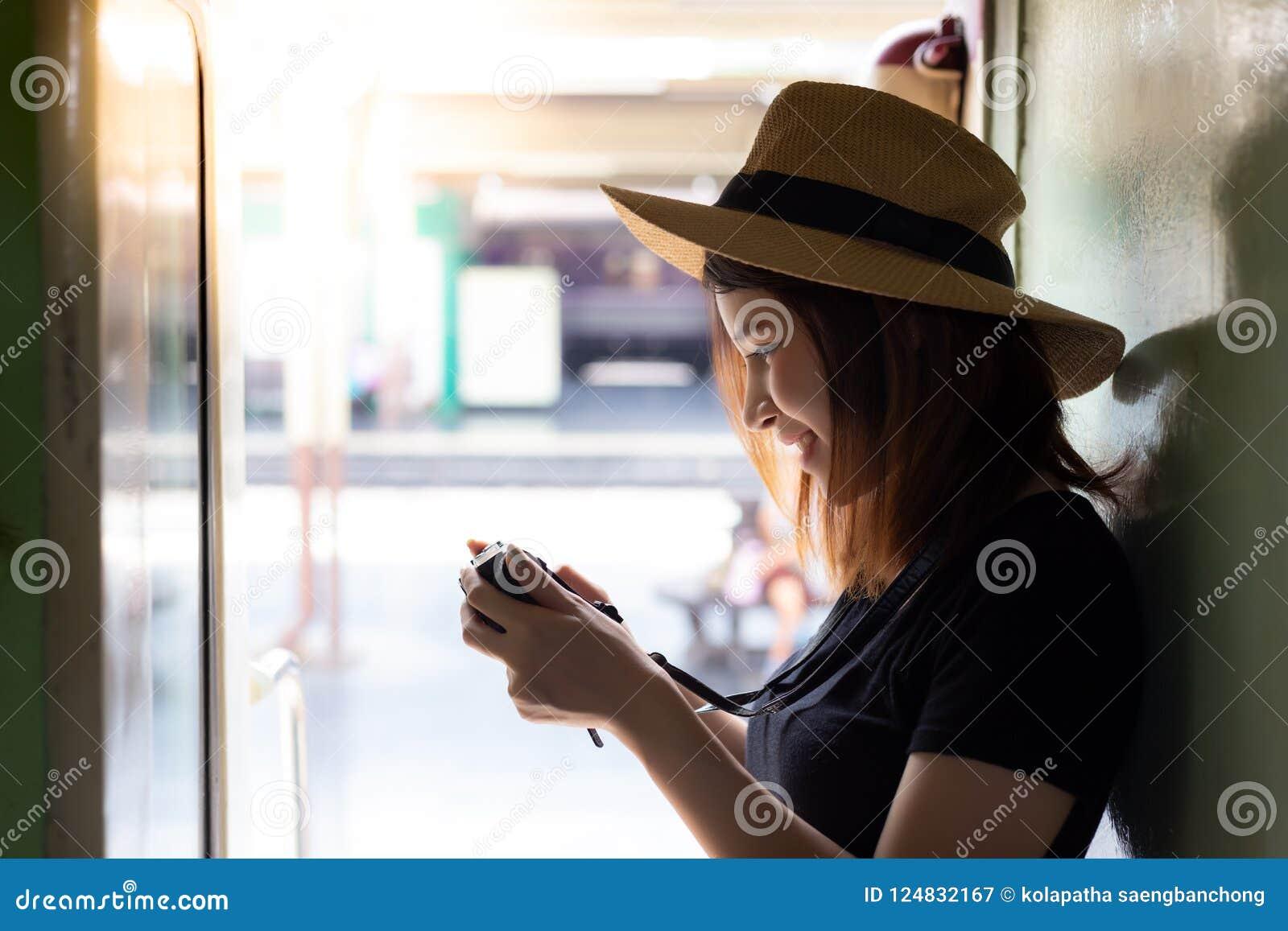 Femme avec du charme de portrait la belle regarde son appareil-photo beau