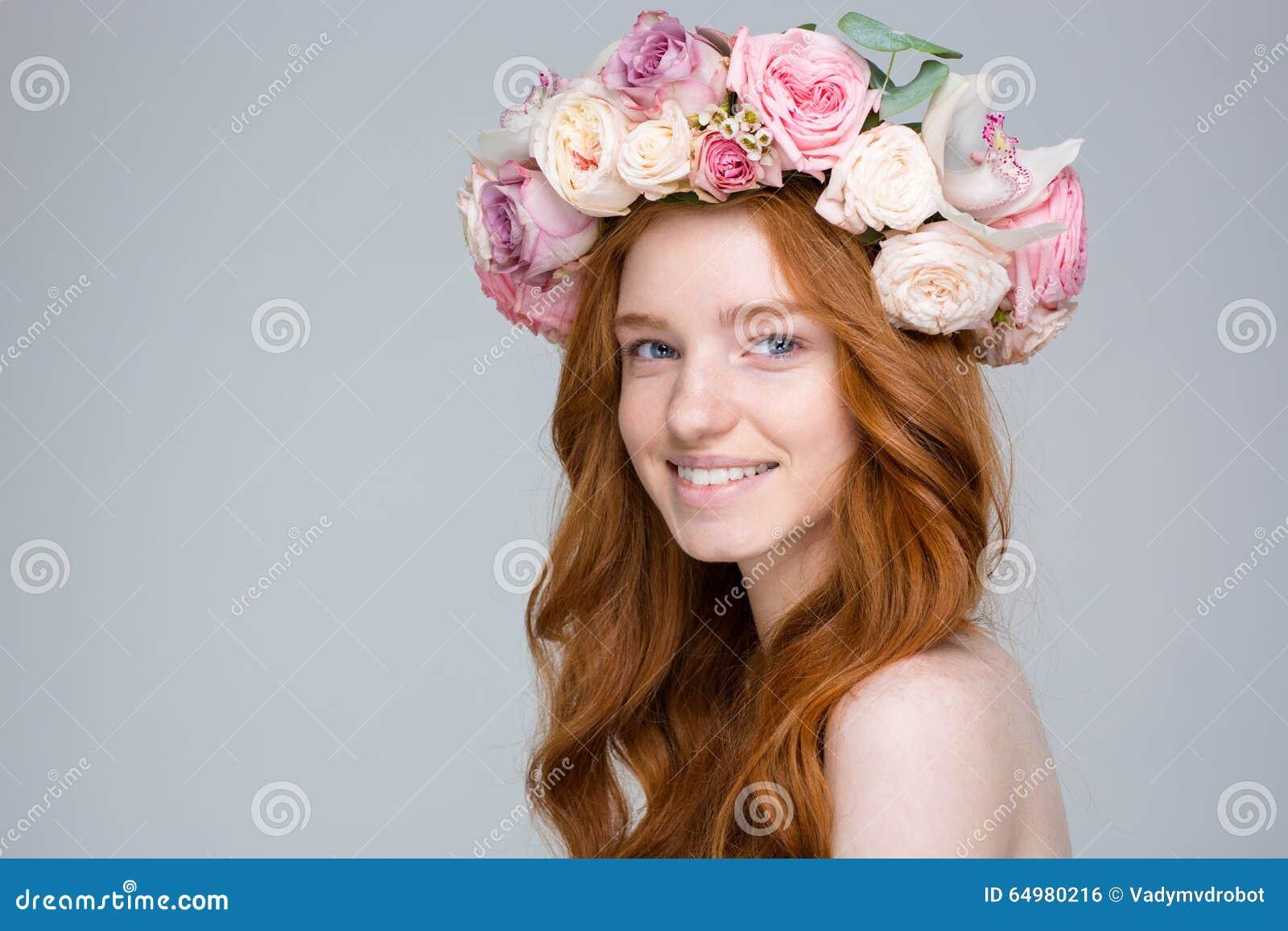 Femme avec du charme gaie en guirlande de fleur au-dessus de fond gris