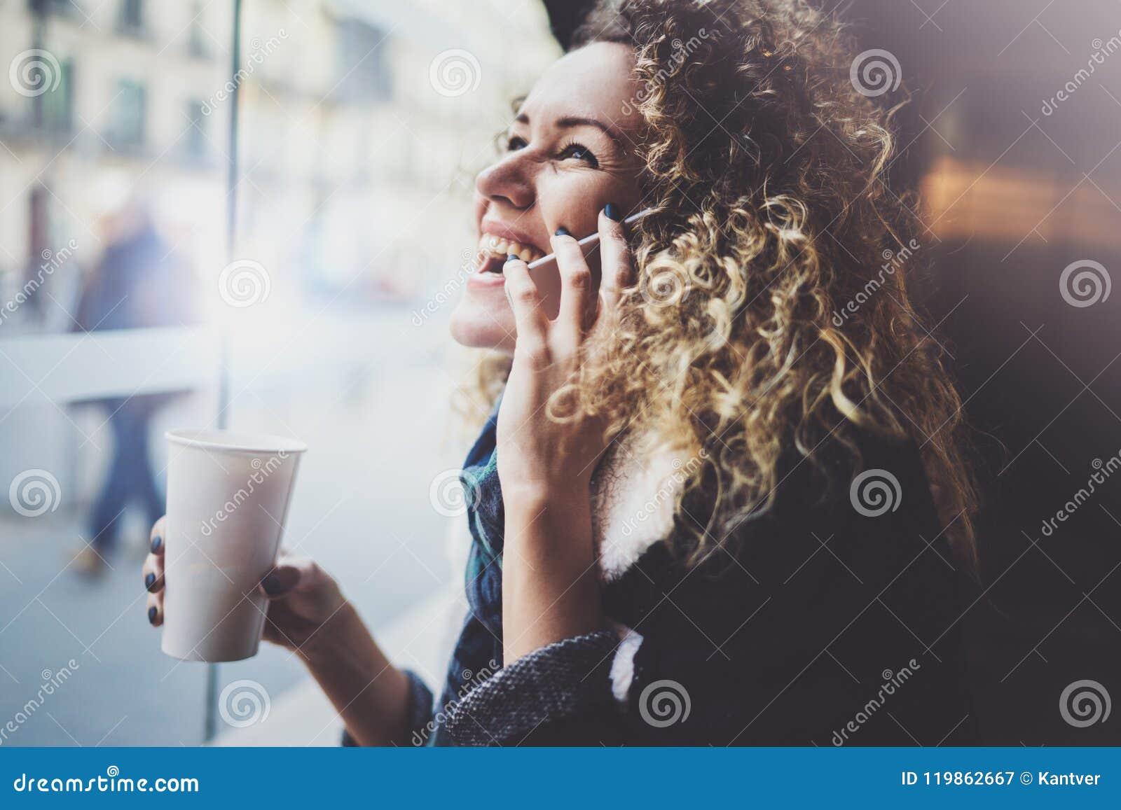 Femme avec du charme avec le beau sourire utilisant le téléphone portable pendant le repos dans le café Fond brouillé