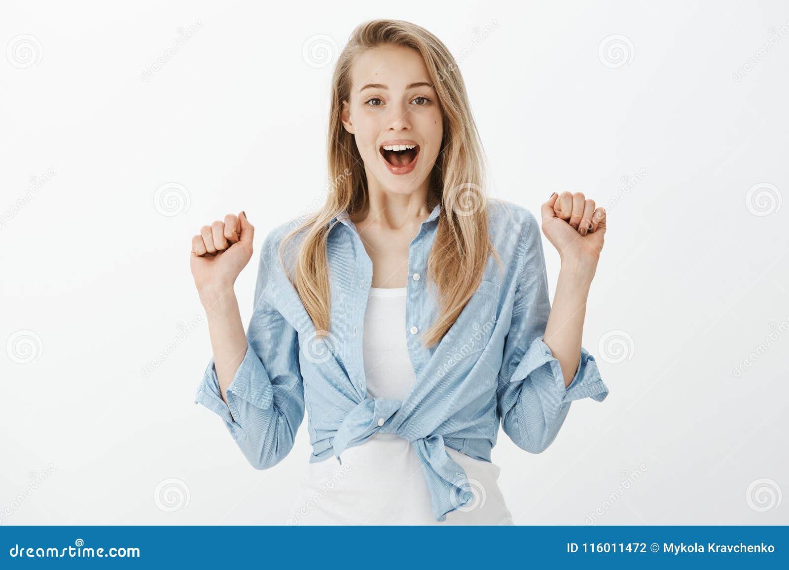 Femme avec du charme triomphante de positif avec les cheveux blonds, soulevant des mains et des poings de serrage de l excitation