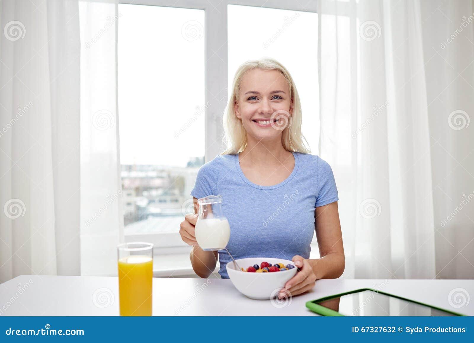 femme avec du lait et des cornflakes mangeant le petit d jeuner photo stock image 67327632. Black Bedroom Furniture Sets. Home Design Ideas