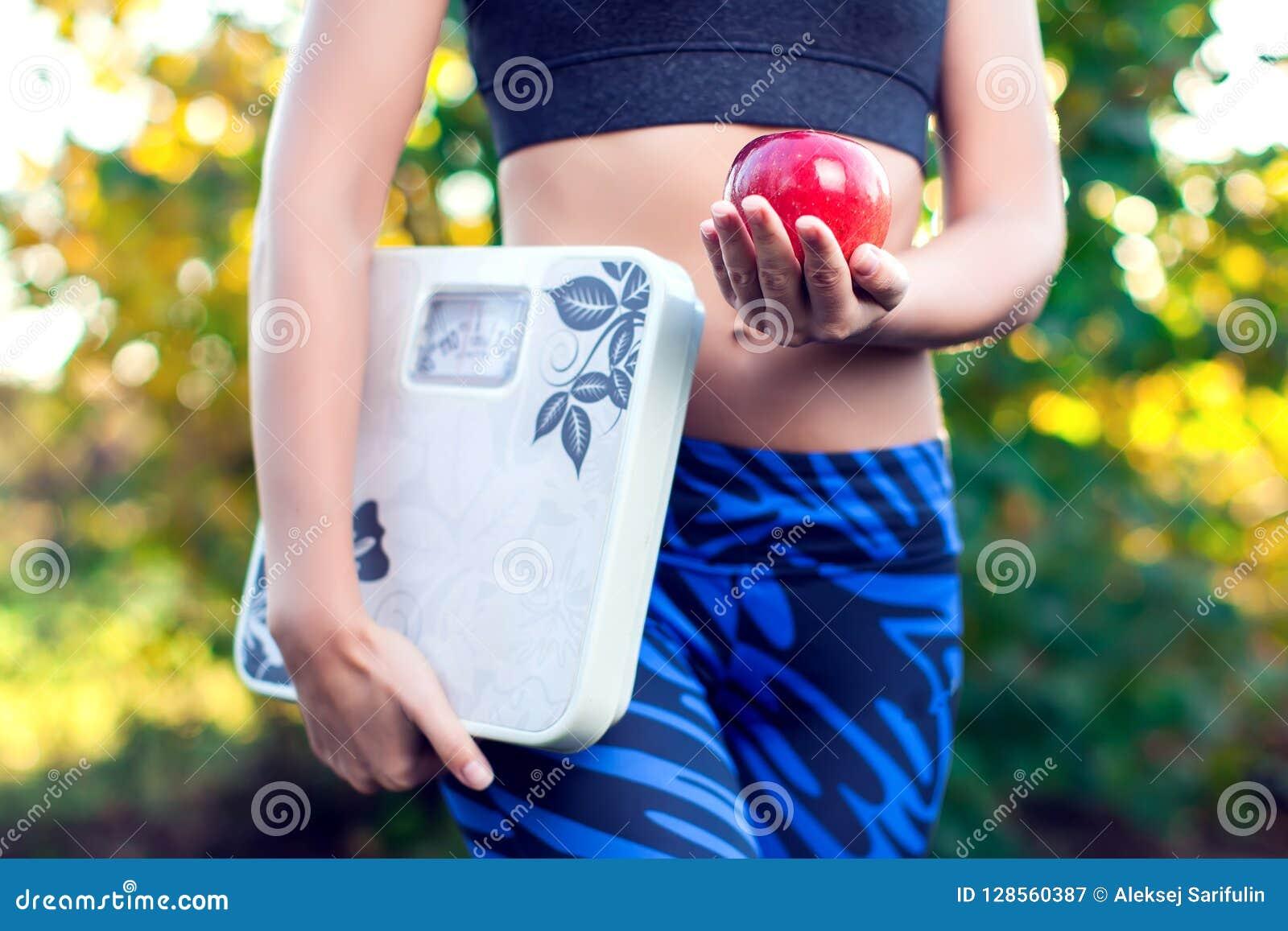 Femme avec l échelle et la pomme rouge extérieures Régime, régime et healt