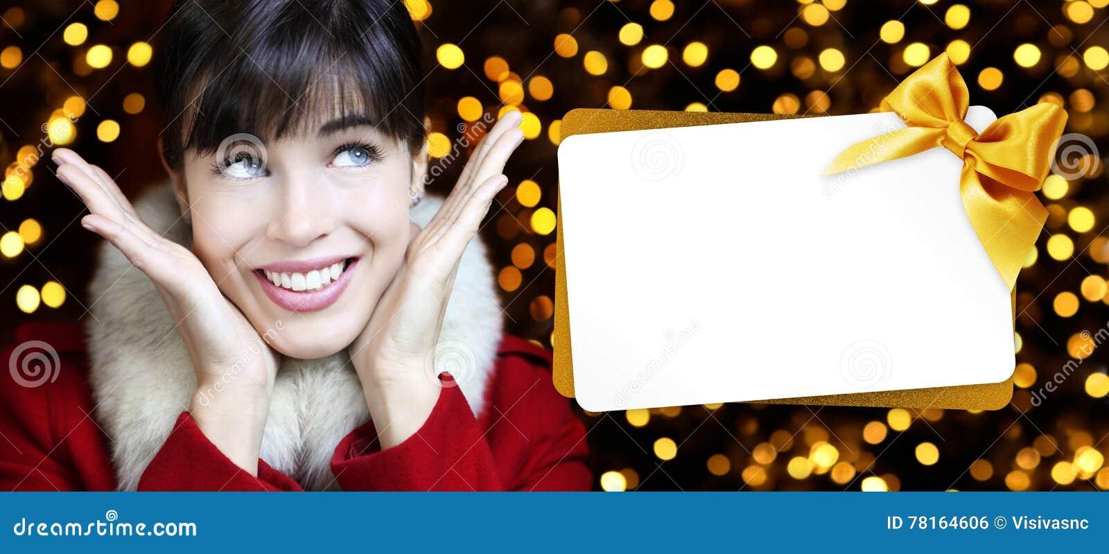 Femme avec la carte cadeaux de Noël dans les lumières d or