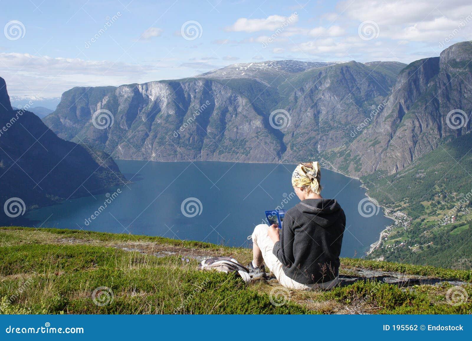 Femme avec la carte se reposant sur le dessus de la montagne