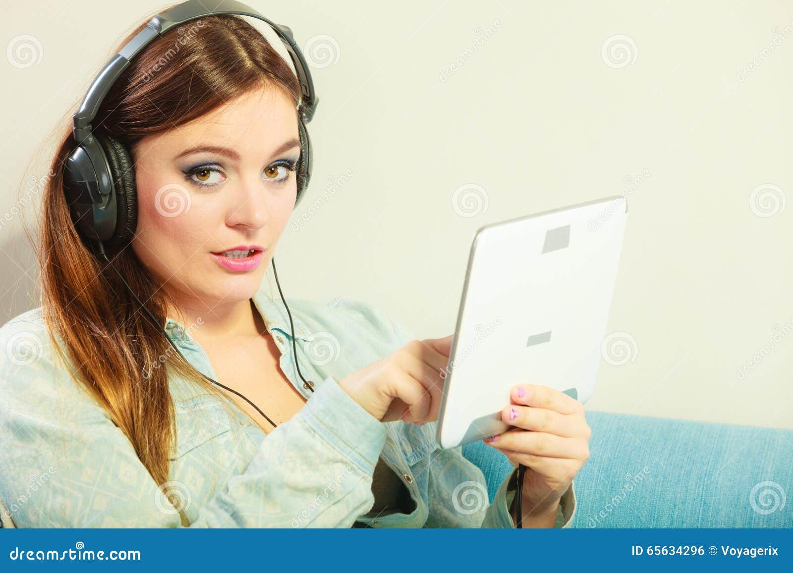 Femme avec la détente d écouteurs de comprimé