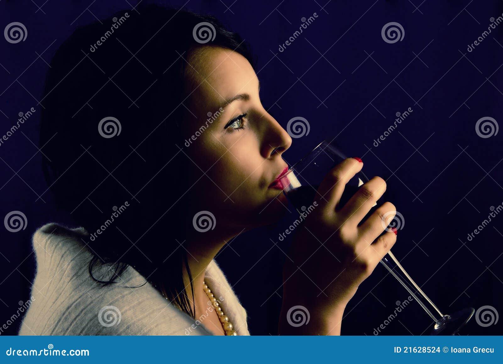Femme avec la glace de vin rouge