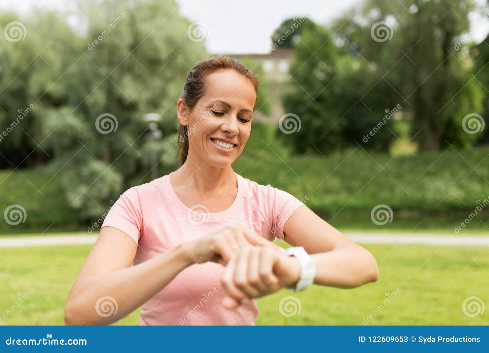 Femme avec la montre ou le traqueur futée de forme physique en parc