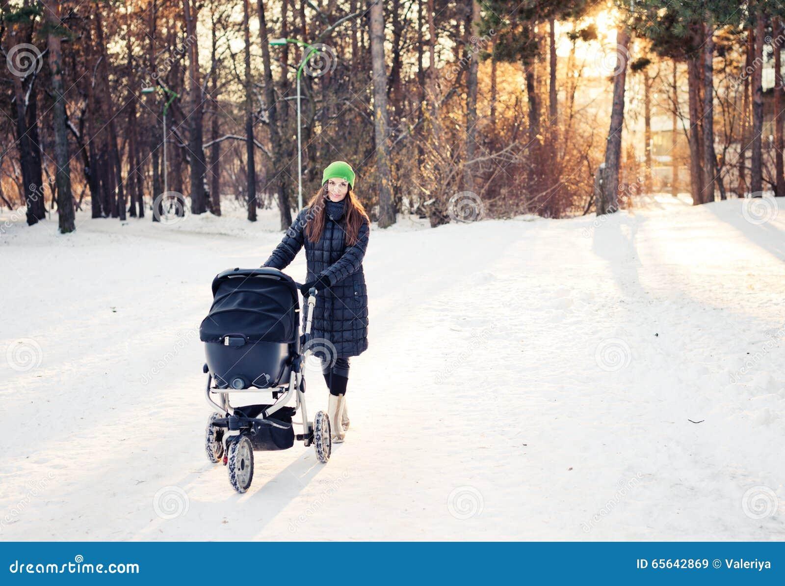 Femme avec la poussette faisant une promenade dedans