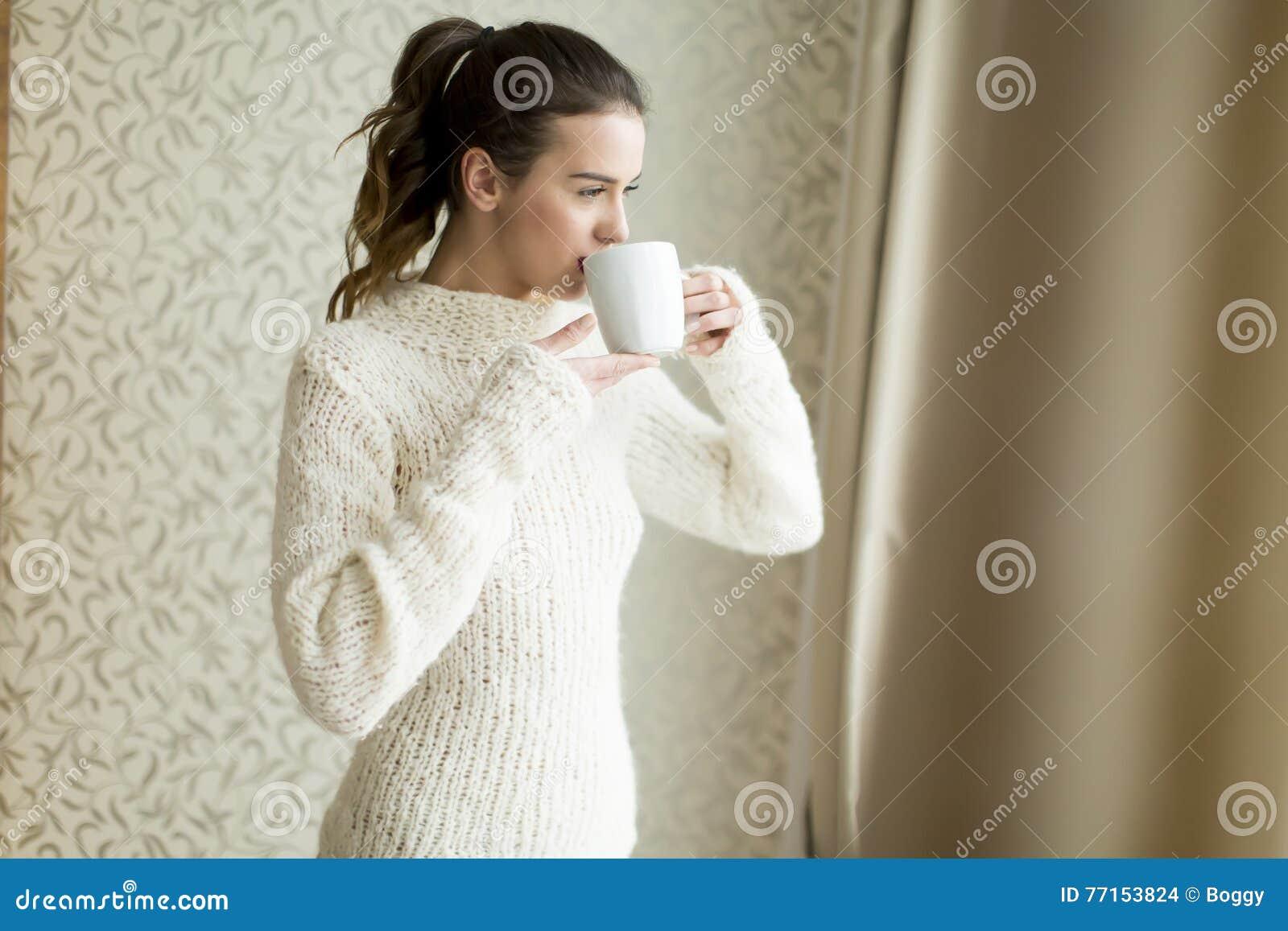Femme avec la tasse par la fenêtre