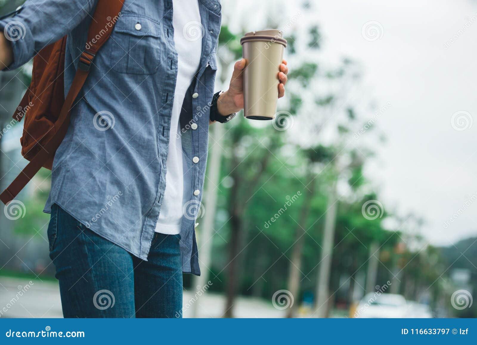 Femme avec la tasse thermo de café