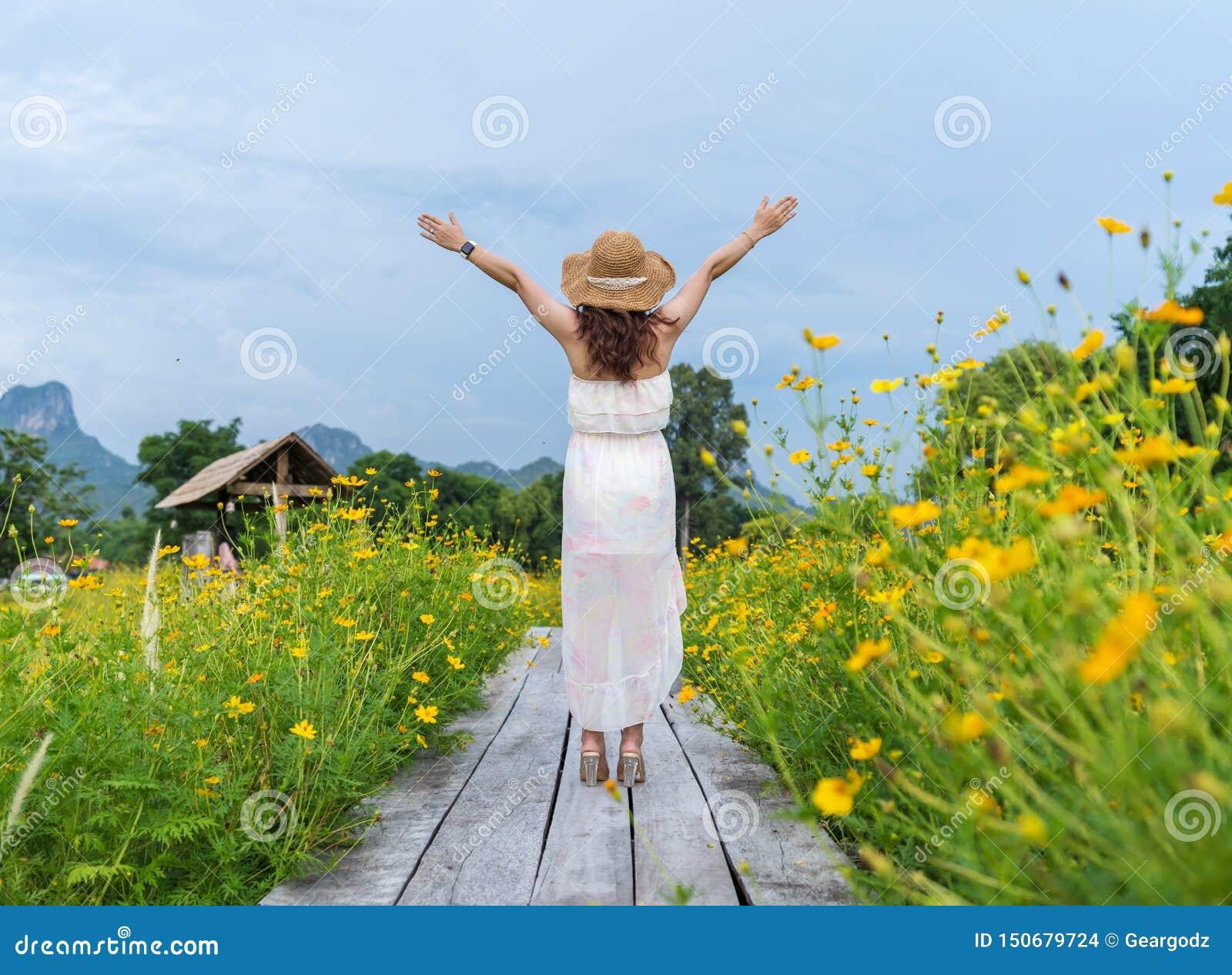 Femme avec le bras augmenté sur le pont en bois avec le gisement de fleur jaune de cosmos