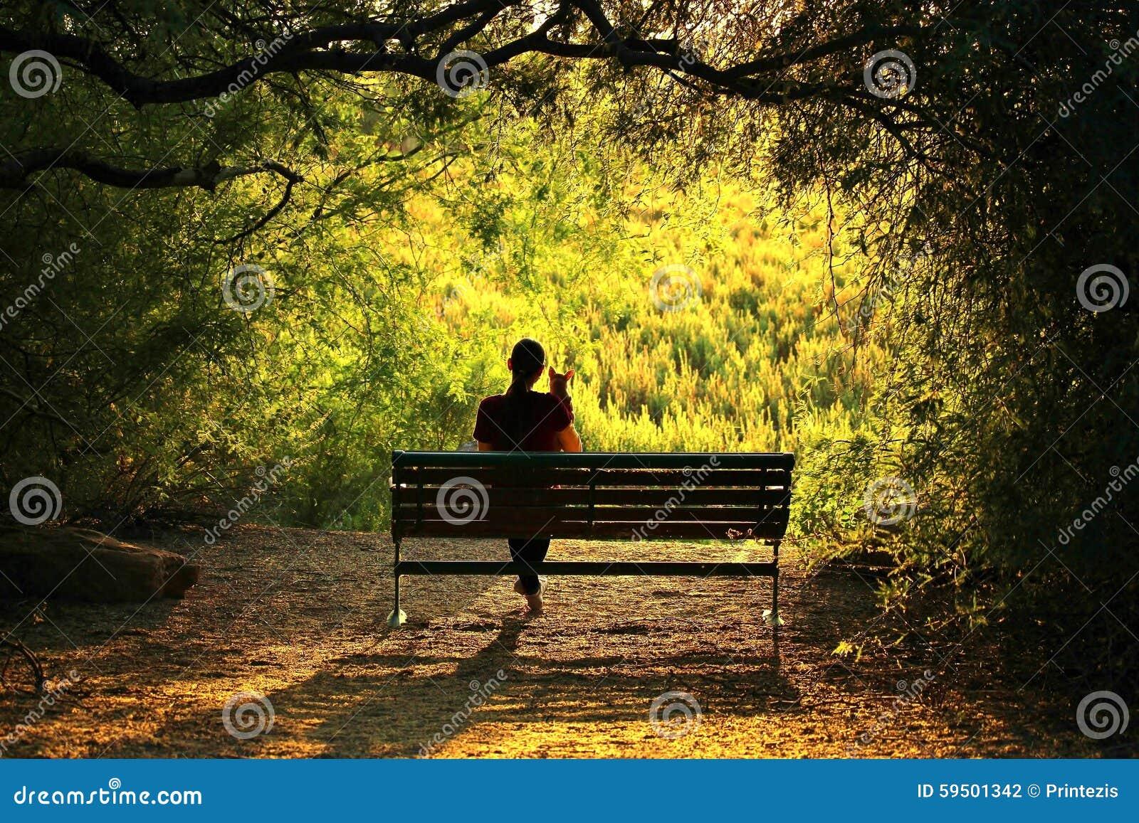 Femme avec le chien se reposant sur un banc