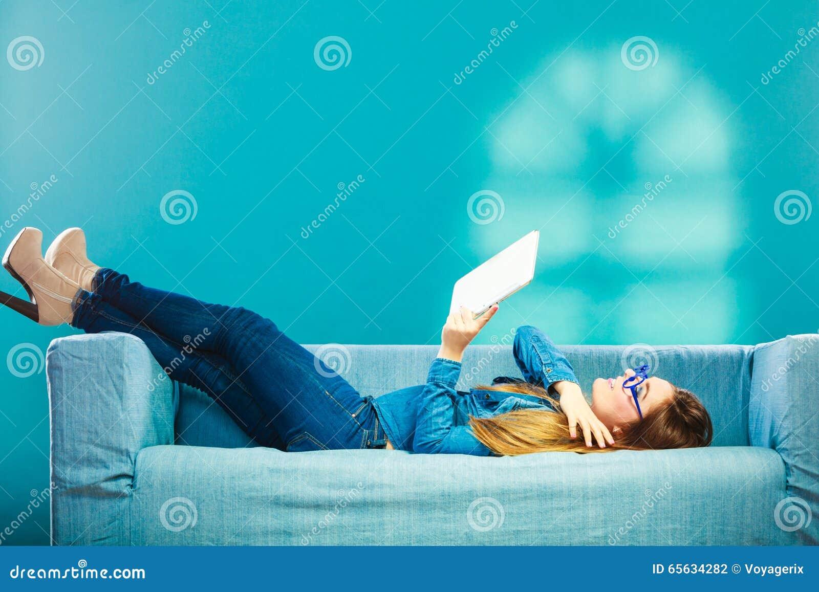 Femme avec le comprimé détendant sur la couleur de bleu de divan