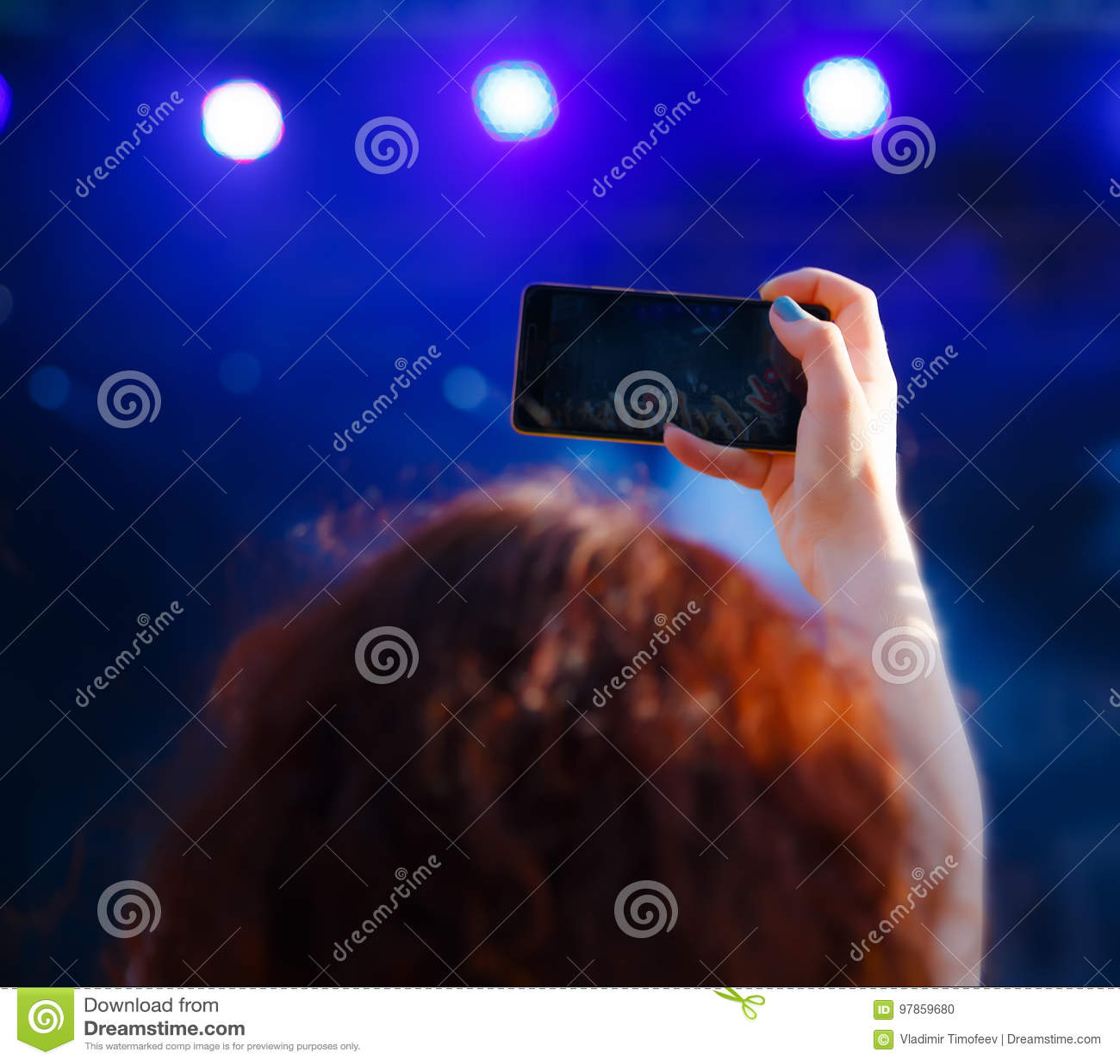 Femme avec le concert de tir de téléphone, vue par derrière, effet de tache floue