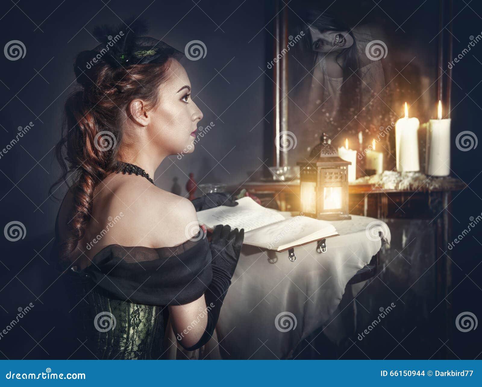 Femme avec le livre dans la rétro robe et le fantôme dans le miroir