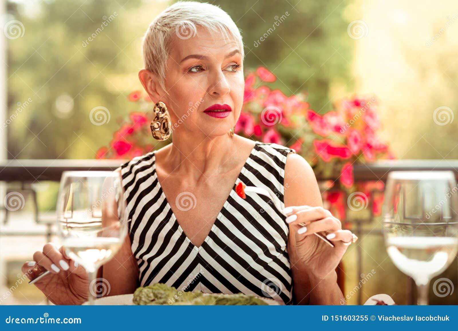 Femme avec le maquillage gentil mangeant de la salade pour le dîner dehors