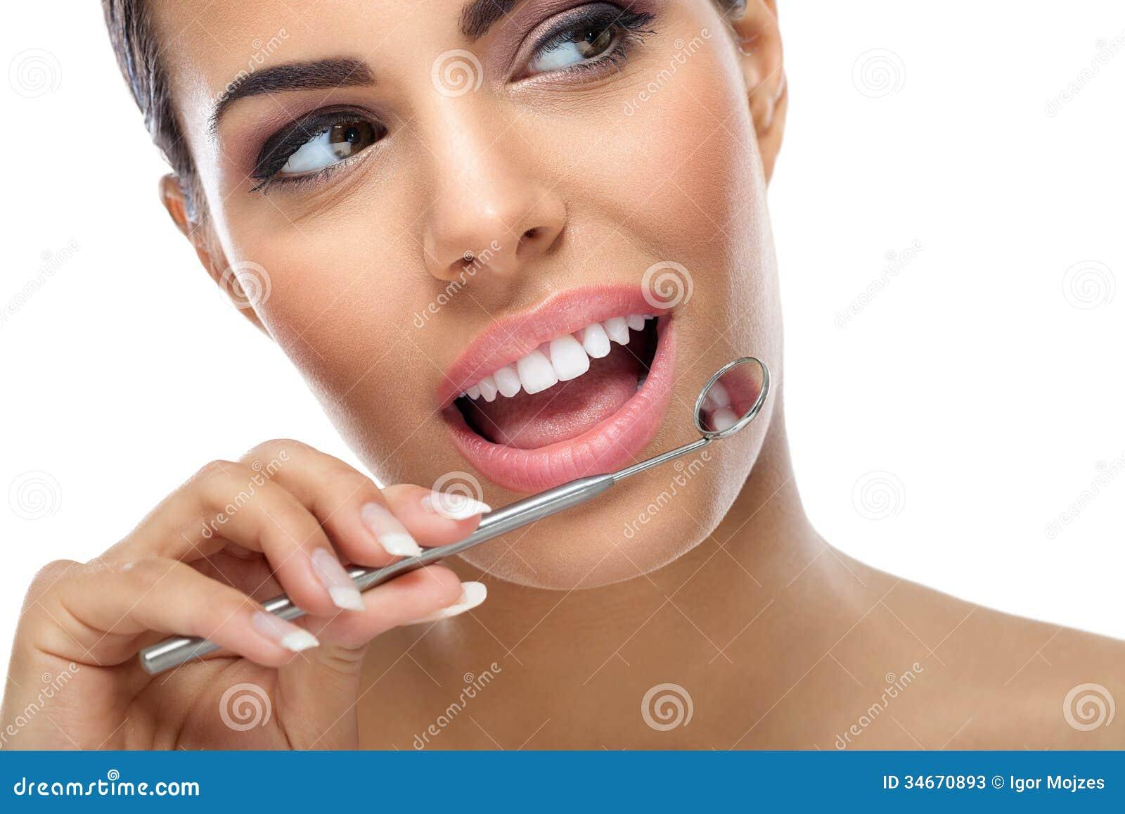 Femme avec le miroir dentaire