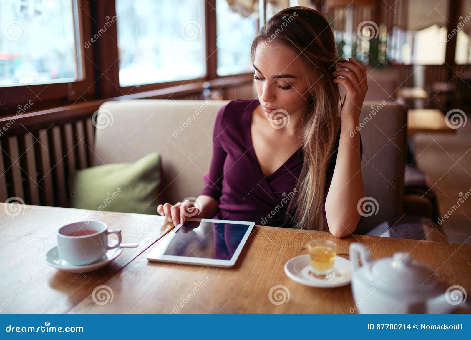 Femme avec le PC de comprimé utilisant l Internet dans le restaurant