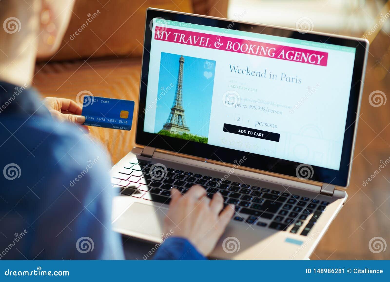 Femme avec le site en ligne de voyage sur l ordinateur portable tenant la carte de crédit bleue