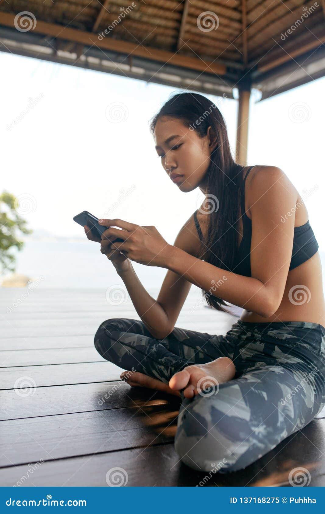 Femme avec le téléphone Fille asiatique dans des vêtements de sport utilisant Smartphone