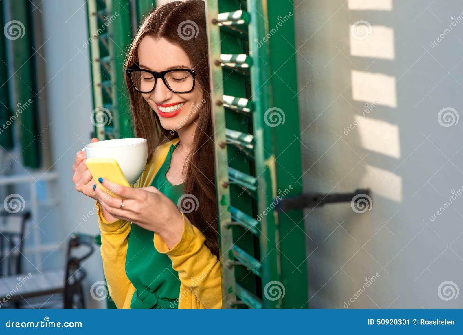 Femme avec le téléphone sur le balcon