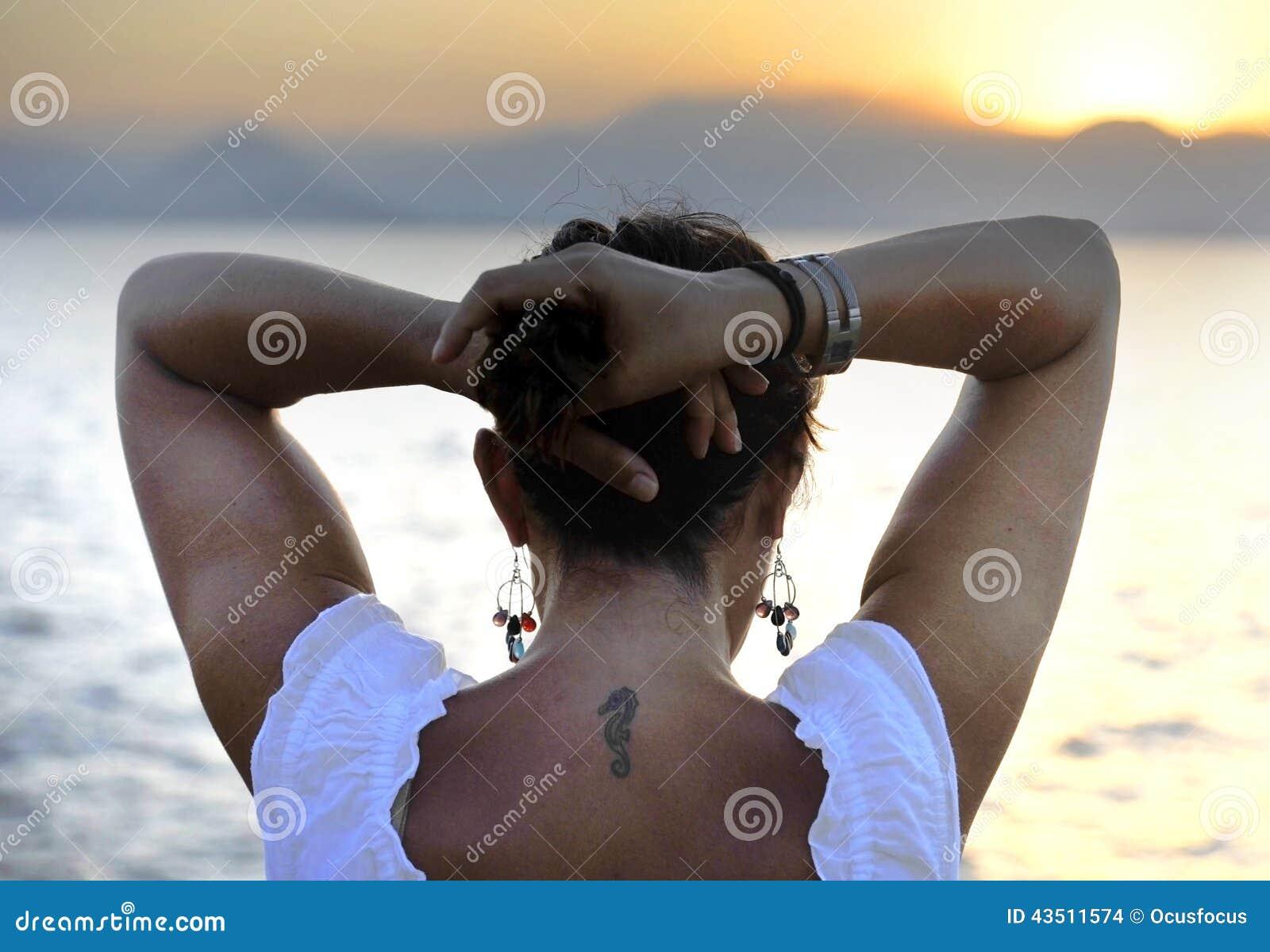 femme avec le tatouage arri re d 39 hippocampe se tenant seul regardant l 39 horizon de mer photo. Black Bedroom Furniture Sets. Home Design Ideas