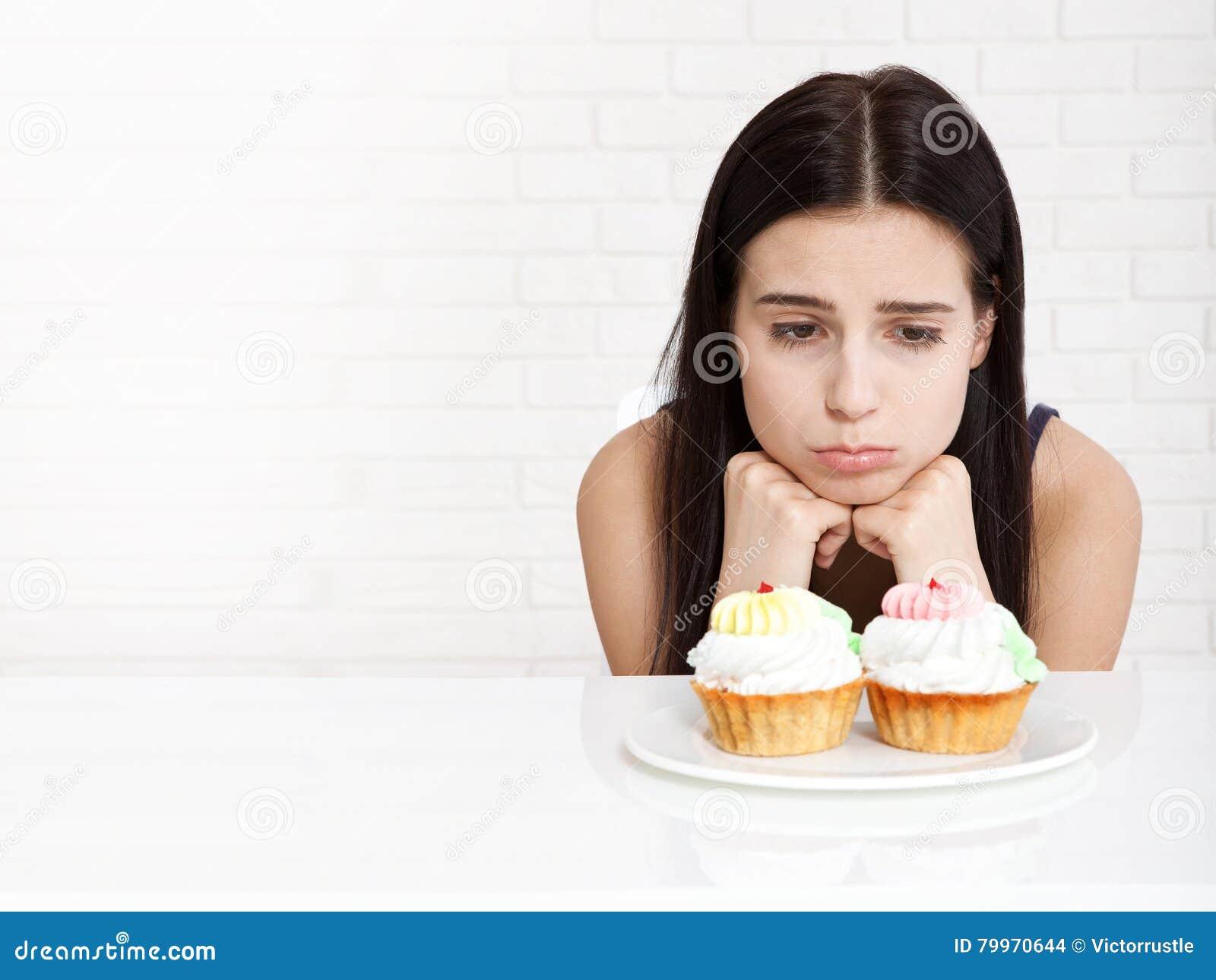 Femme avec le visage de plan rapproché de gâteau Les belles femmes regarde tristement le gâteau Femme asiatique Foyer sélectif