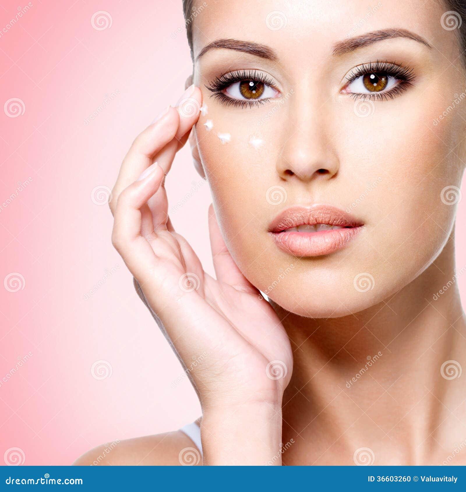 Femme avec le visage sain appliquant la crème cosmétique sous les yeux