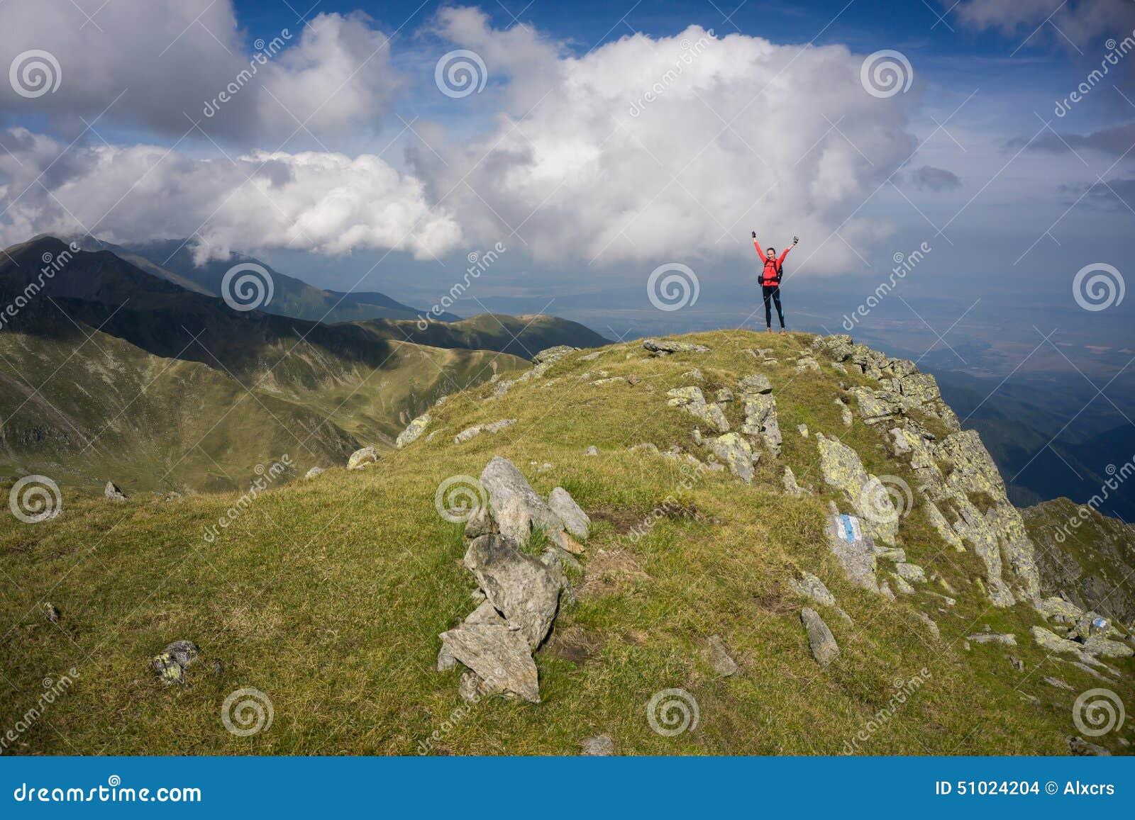Femme avec les bras étirés dans les montagnes