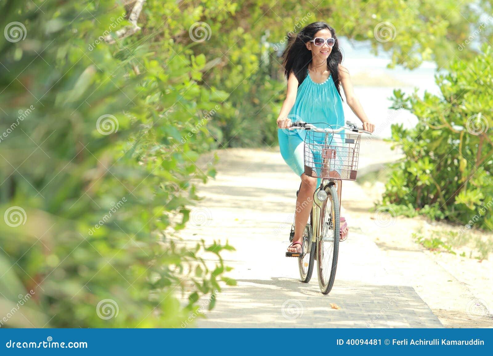 Femme ayant la bicyclette d équitation d amusement à la plage