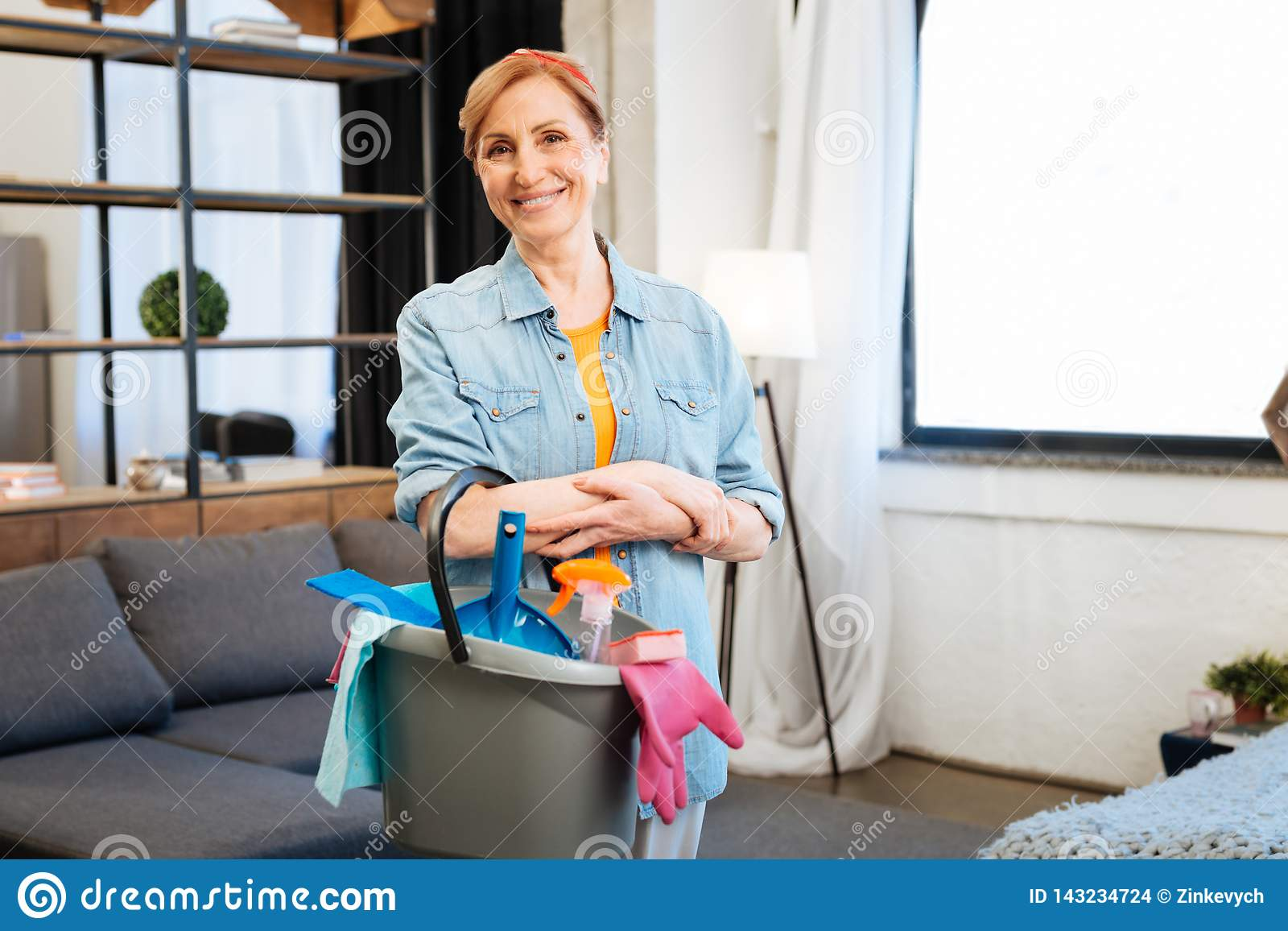 Femme belle positive avec la position large de sourire au milieu de l appartement