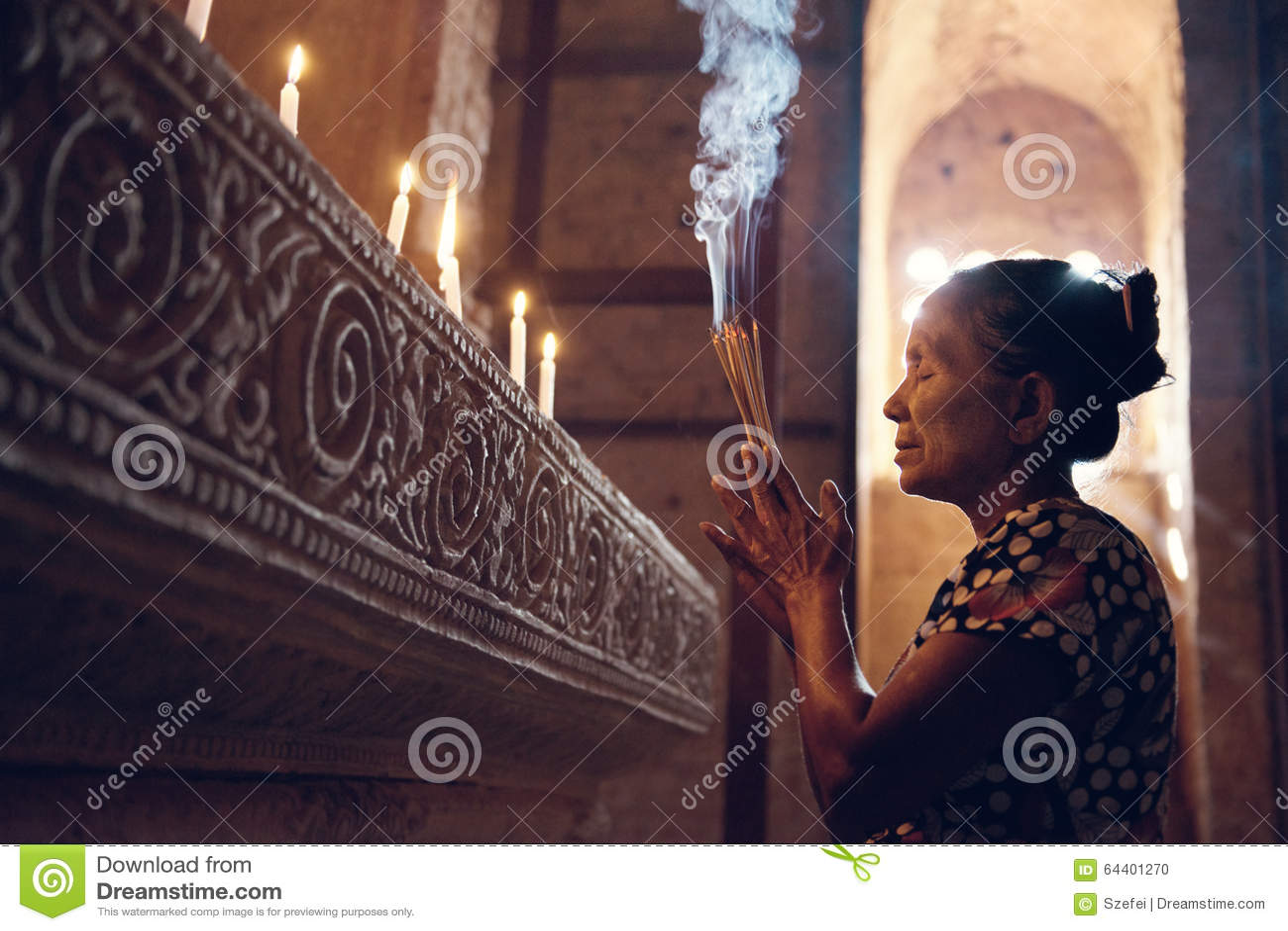 Femme birmanne priant dans le temple